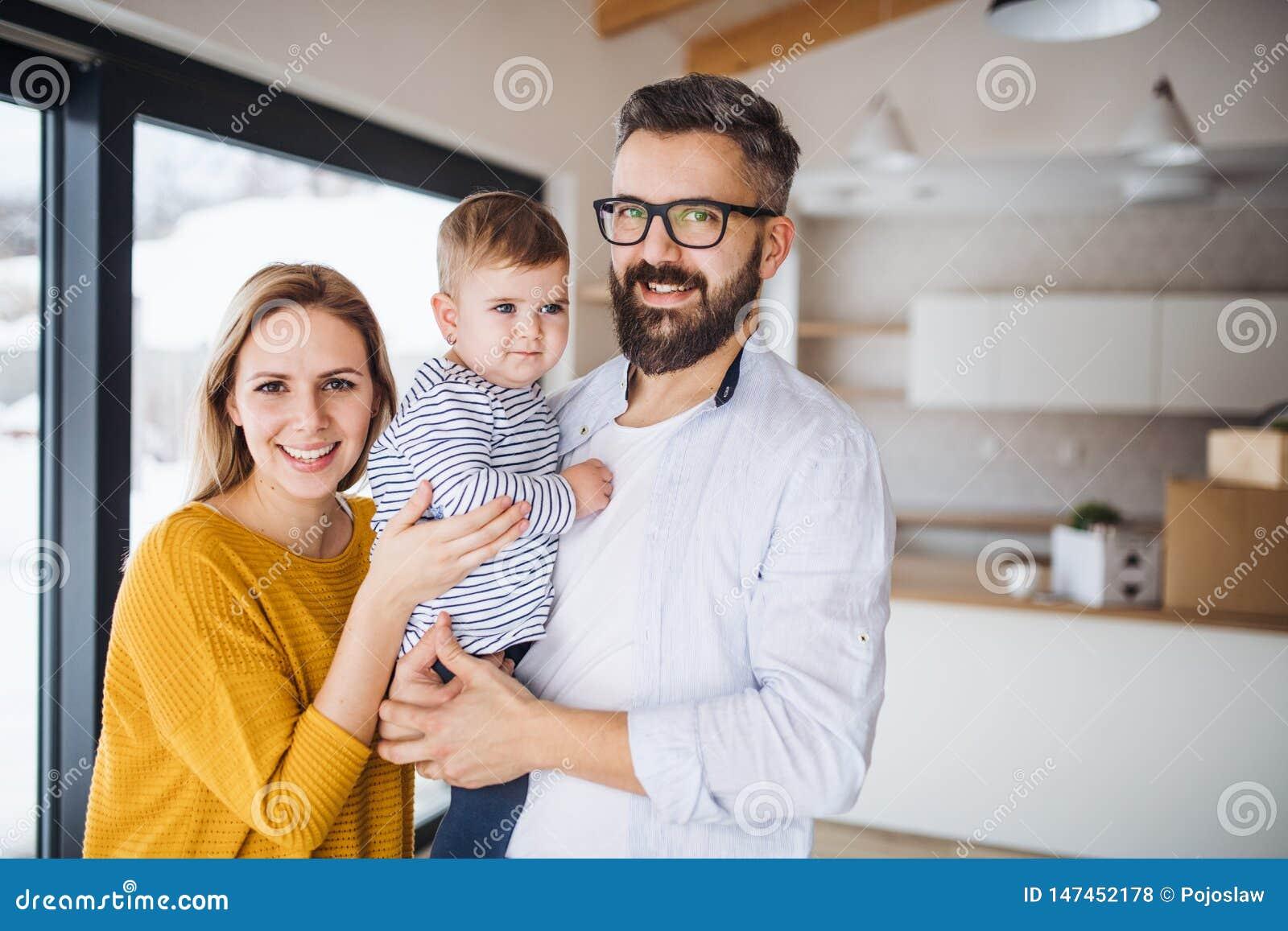 Ένα πορτρέτο της νέας οικογένειας με ένα κορίτσι μικρών παιδιών που κινείται στο νέο σπίτι