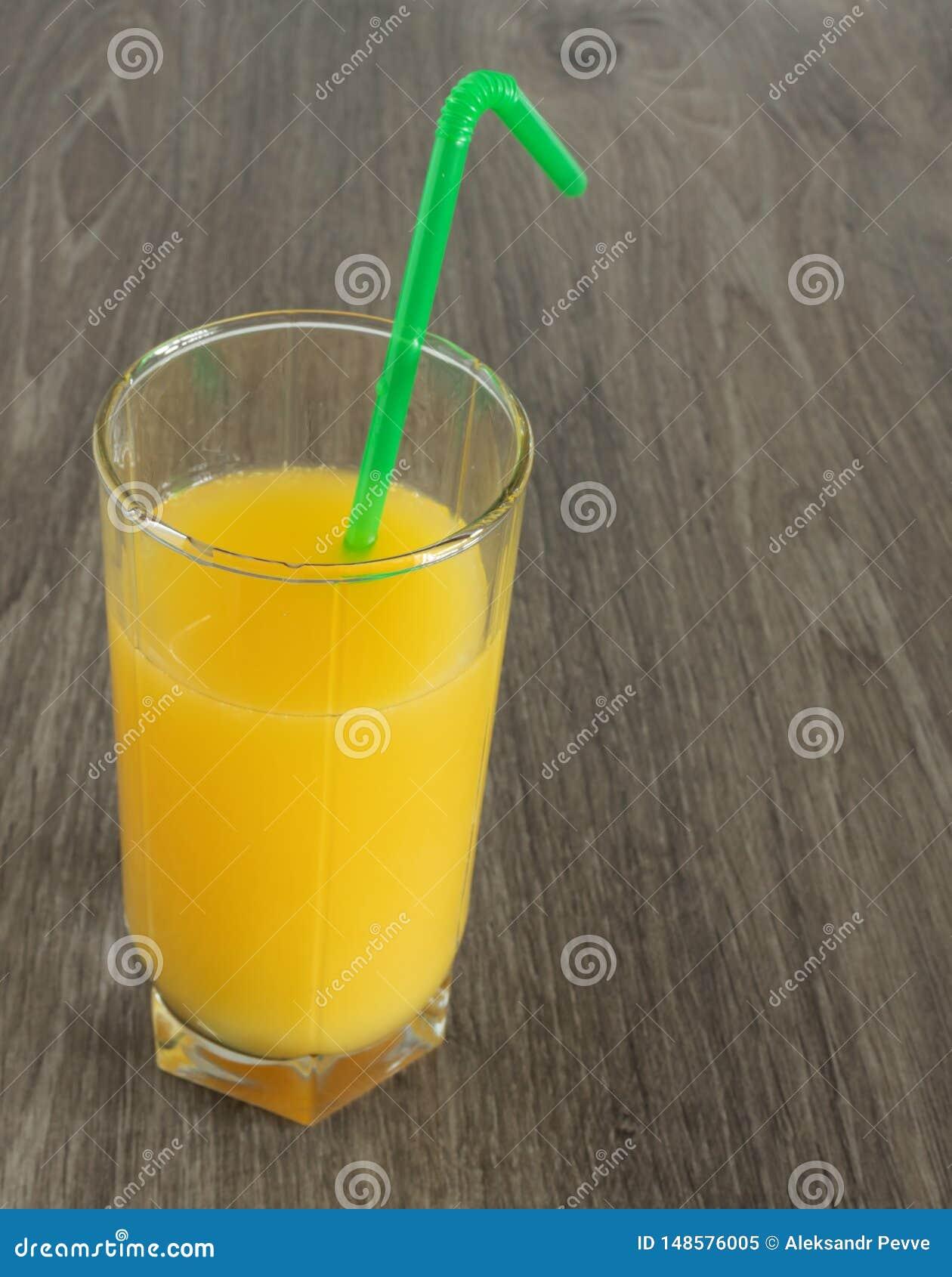 Ένα ποτήρι του χυμού από πορτοκάλι με ένα άχυρο σε ένα ξύλινο υπόβαθρο