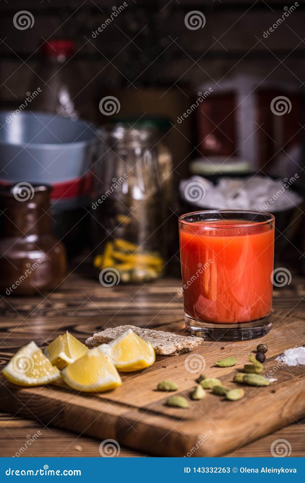 Ένα ποτήρι του χυμού ντοματών σε έναν ξύλινο πίνακα με τις φέτες λεμονιών, το άλας και τους σπόρους κολοκύθας