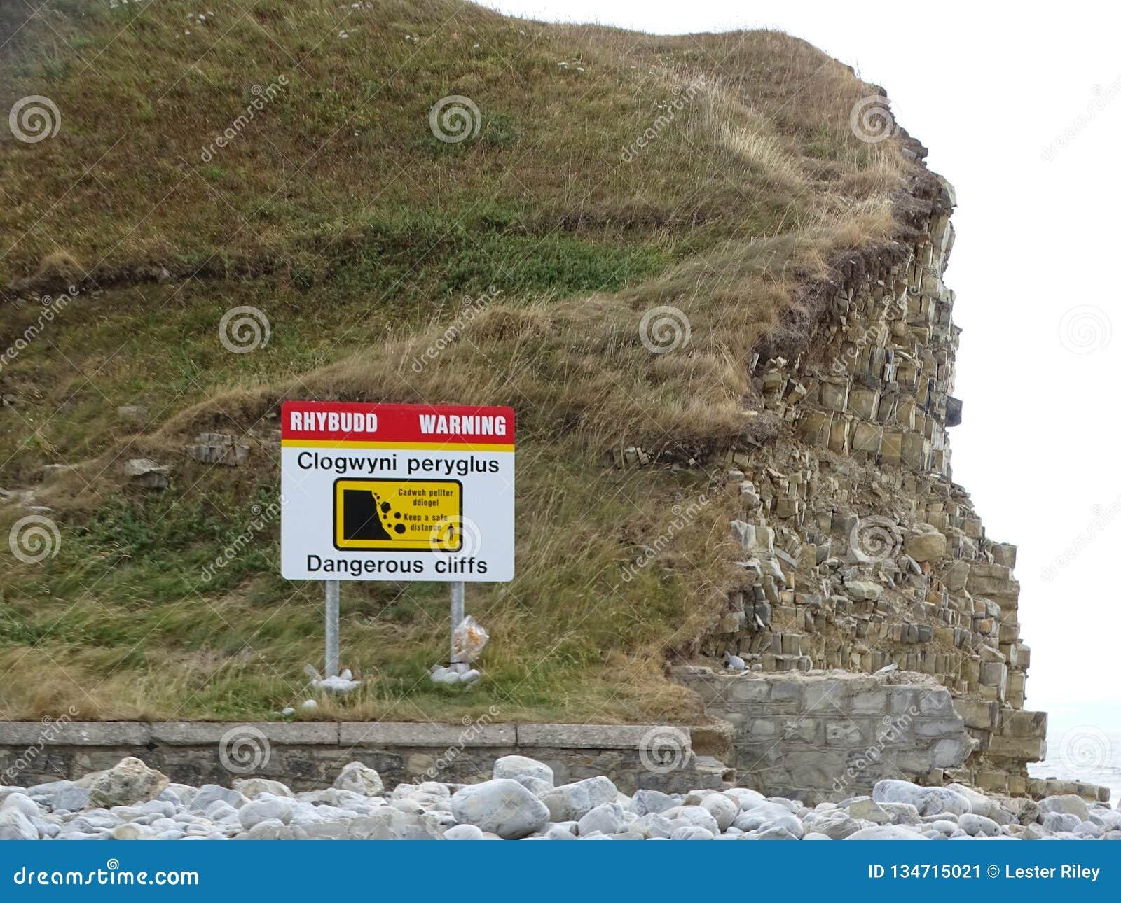 Ένα σημάδι που απεικονίζει τους επικίνδυνους απότομους βράχους σε μια παραλία χαλικιών στο UK