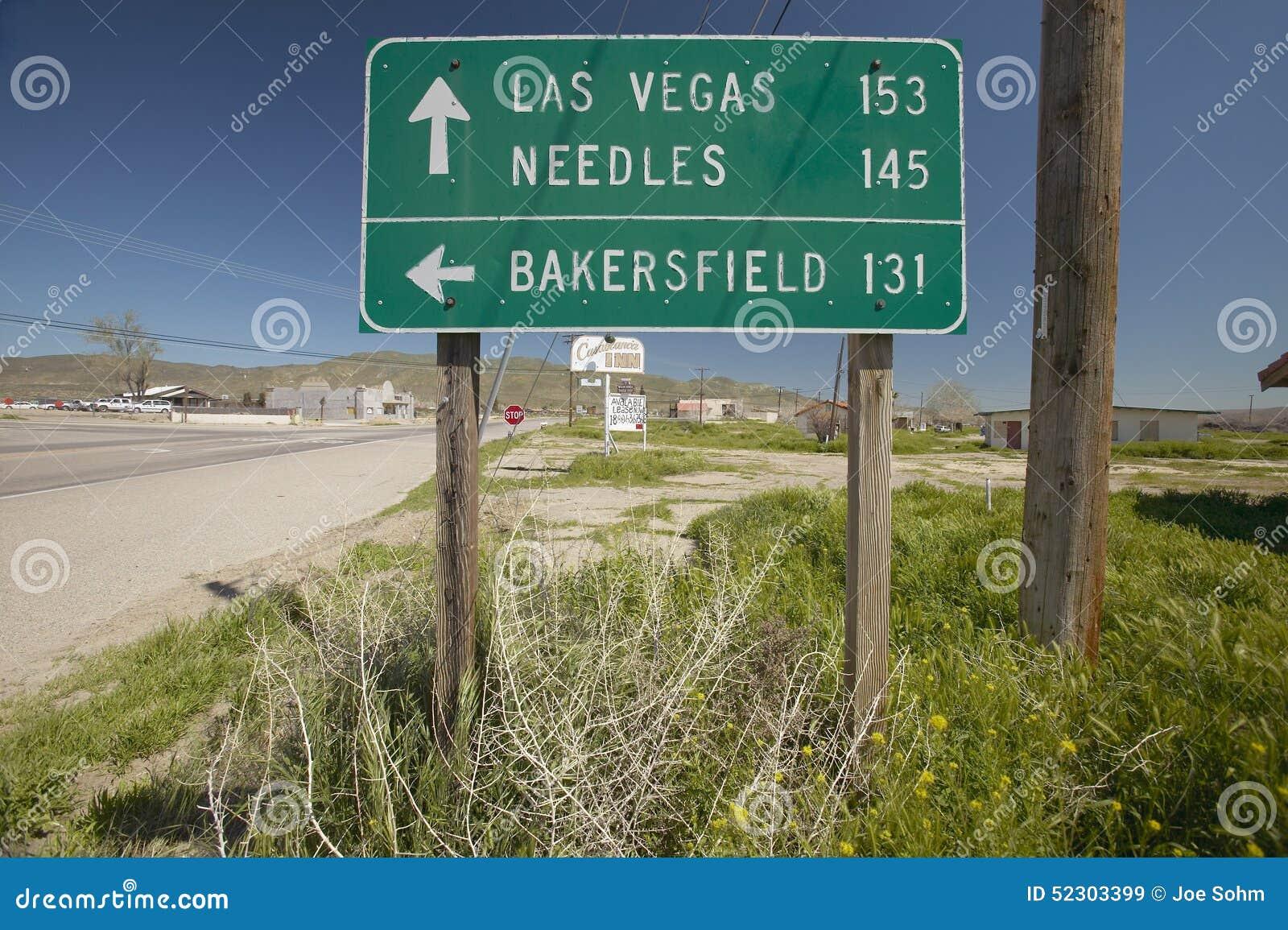 Ένα σημάδι εθνικών οδών που δείχνει το Λας Βέγκας, το Bakersfield και τις βελόνες, ασβέστιο