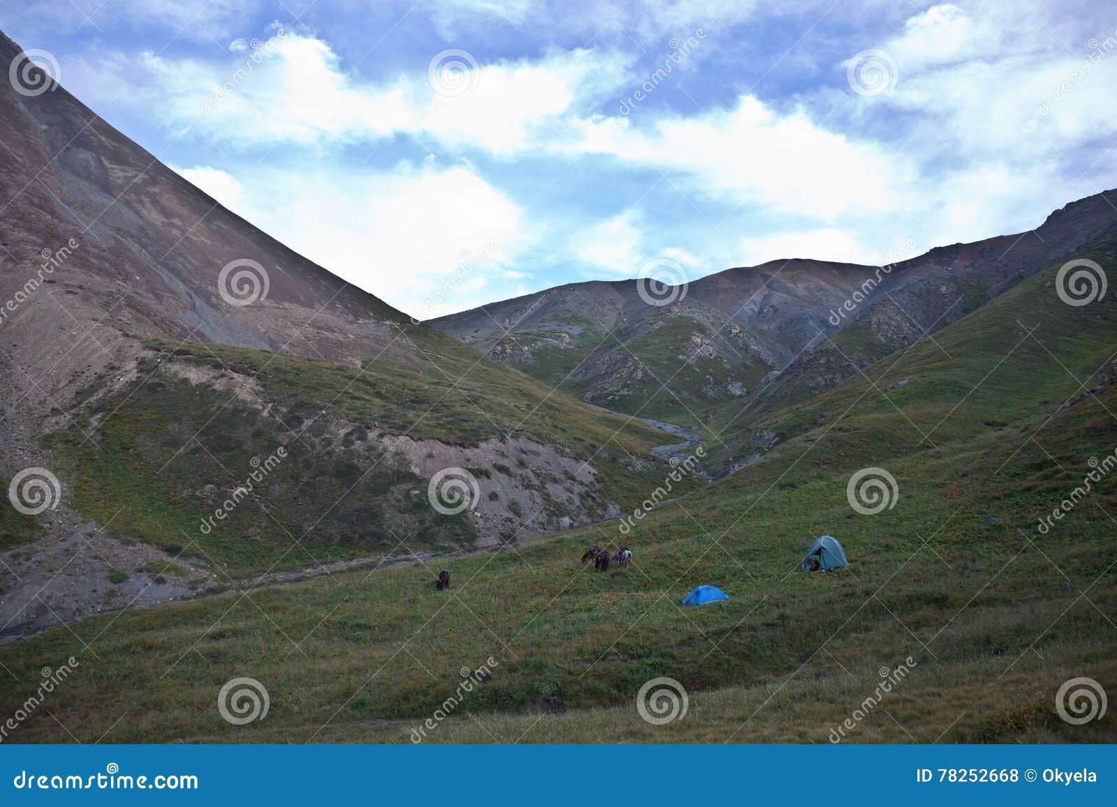 Ένα στρατόπεδο των κυνηγών και των αλόγων που βόσκουν στα βουνά
