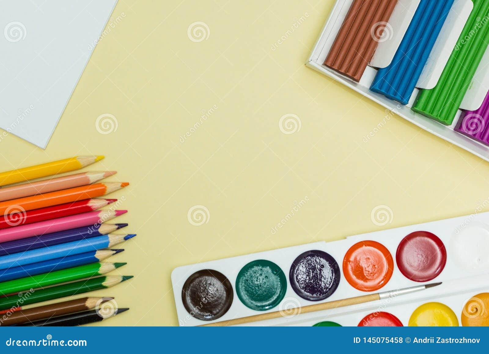 Ένα σύνολο για τη δημιουργικότητα και το σχέδιο: χρώματα watercolor, plasticine και πολύχρωμα μολύβια σε ένα κίτρινο υπόβαθρο r