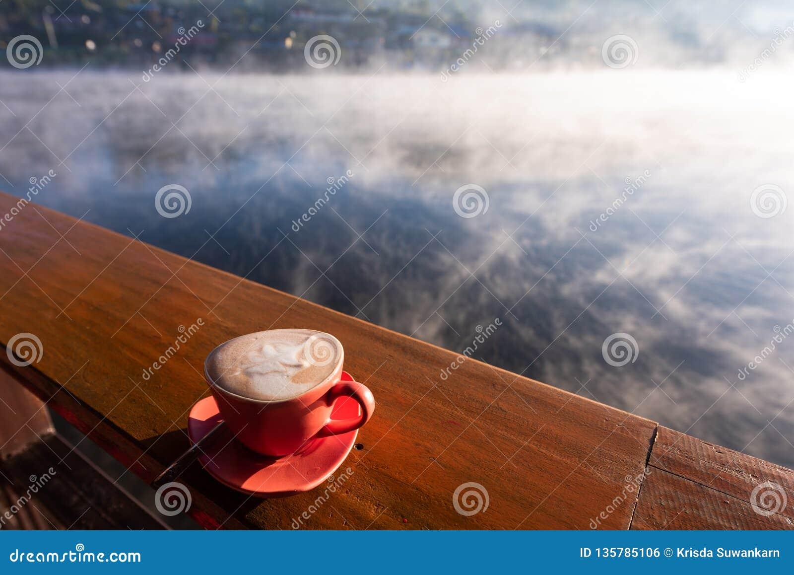 Ένα φλιτζάνι του καφέ στον ξύλινο πίνακα με τον ατμό πέρα από τη λίμνη στο ταϊλανδικό χωριό Rak