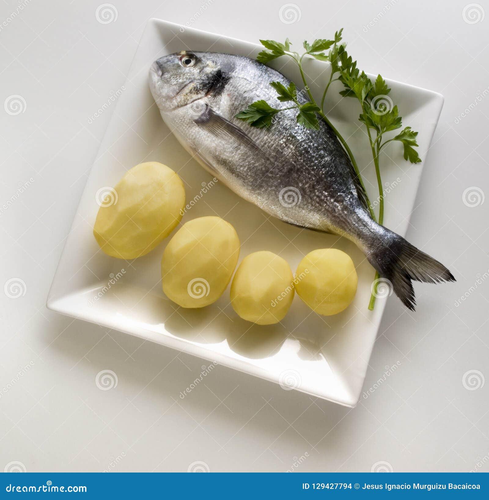 Ένα φρέσκο χρυσό ψάρι που περιβάλλονται από τις πατάτες και ένας κλάδος του μαϊντανού