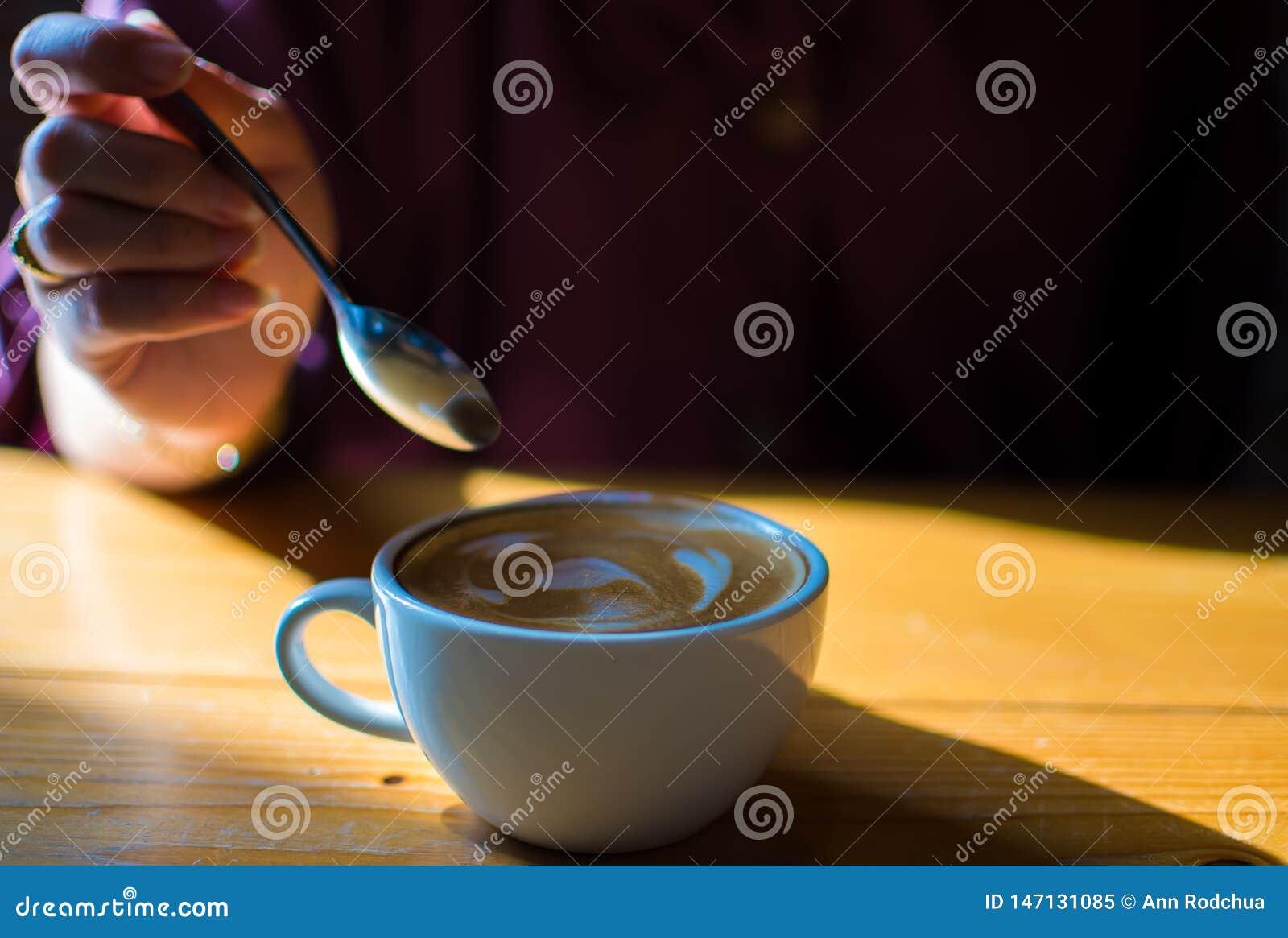 Ένα χέρι κρατά ένα κουτάλι για να δοκιμάσει latte τον καφέ