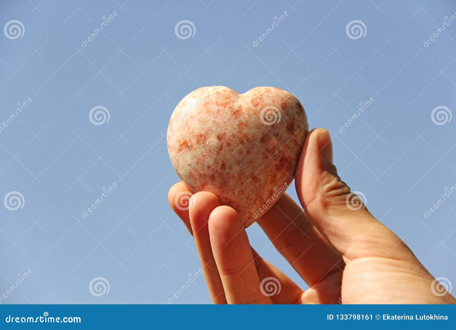 Ένα χέρι κρατά μια καρδιά φιαγμένη από φυσική πέτρα rhodochrosite ενάντια