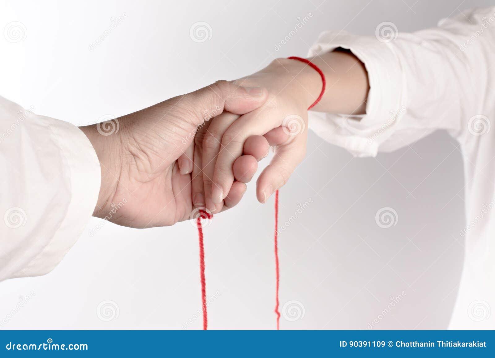 Ένα χέρι του ζεύγους αγγίζει το ένα το άλλο Η πίστη του κόκκινου νήματος φέρνει το πεπρωμένο
