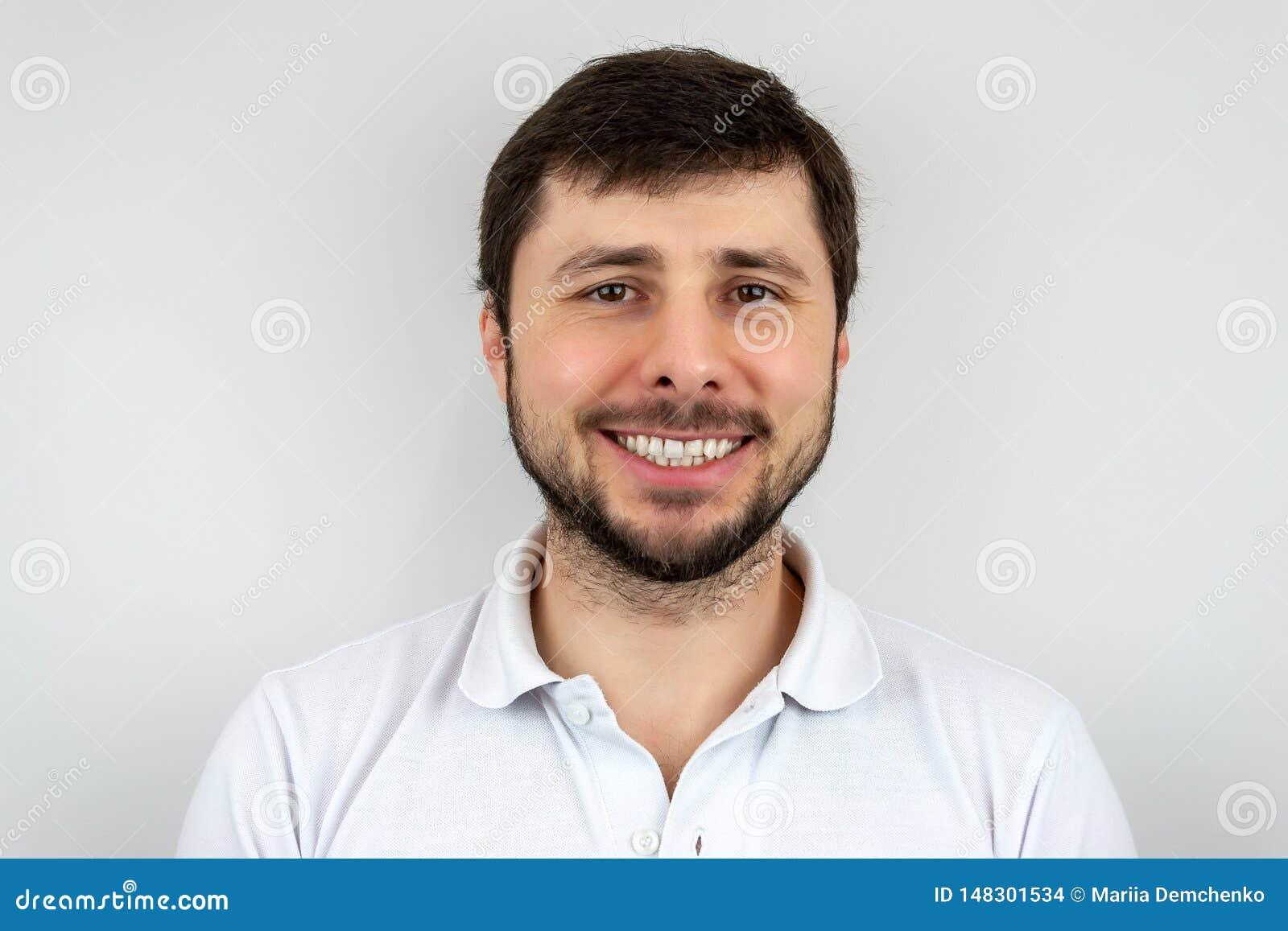Ένα χαμόγελο του πολύ ευτυχούς όμορφου γενειοφόρου ατόμου με τα καφετιά μάτια σε μια άσπρη μπλούζα