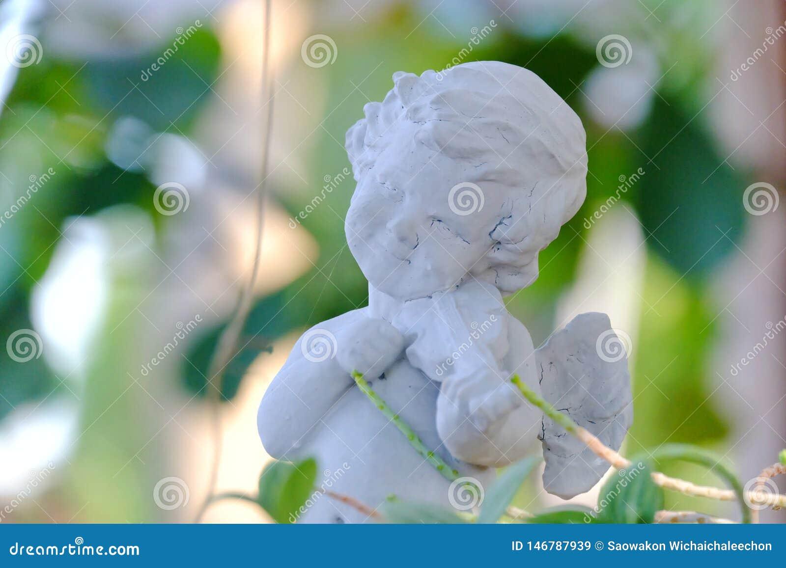 Ένα χαριτωμένο άσπρο γλυπτό cupid που παίζει ένα βιολί και που κοιτάζει επίμονα σε έναν πράσινο κήπο
