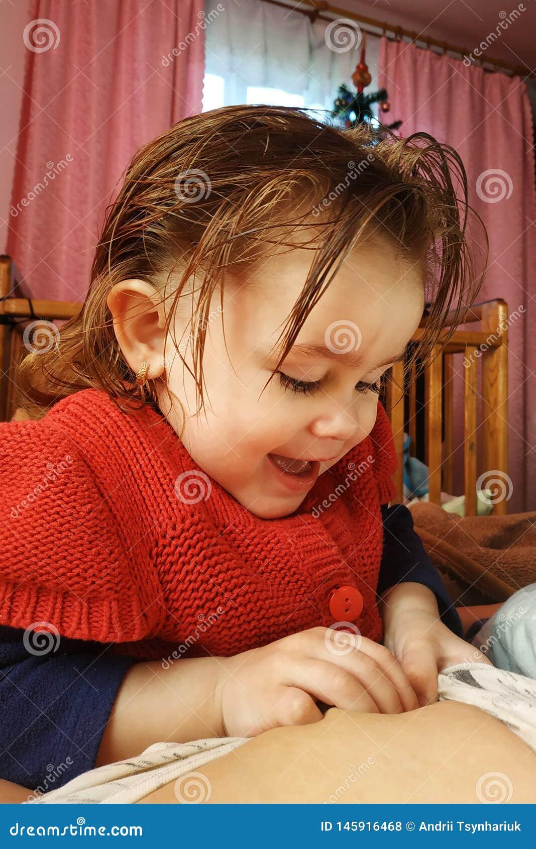Ένα 2χρονο κορίτσι βρίσκεται στη μητέρα και πίνει το μητρικό γάλα, ο χρόνος της ενότητας της μητέρας και του παιδιού