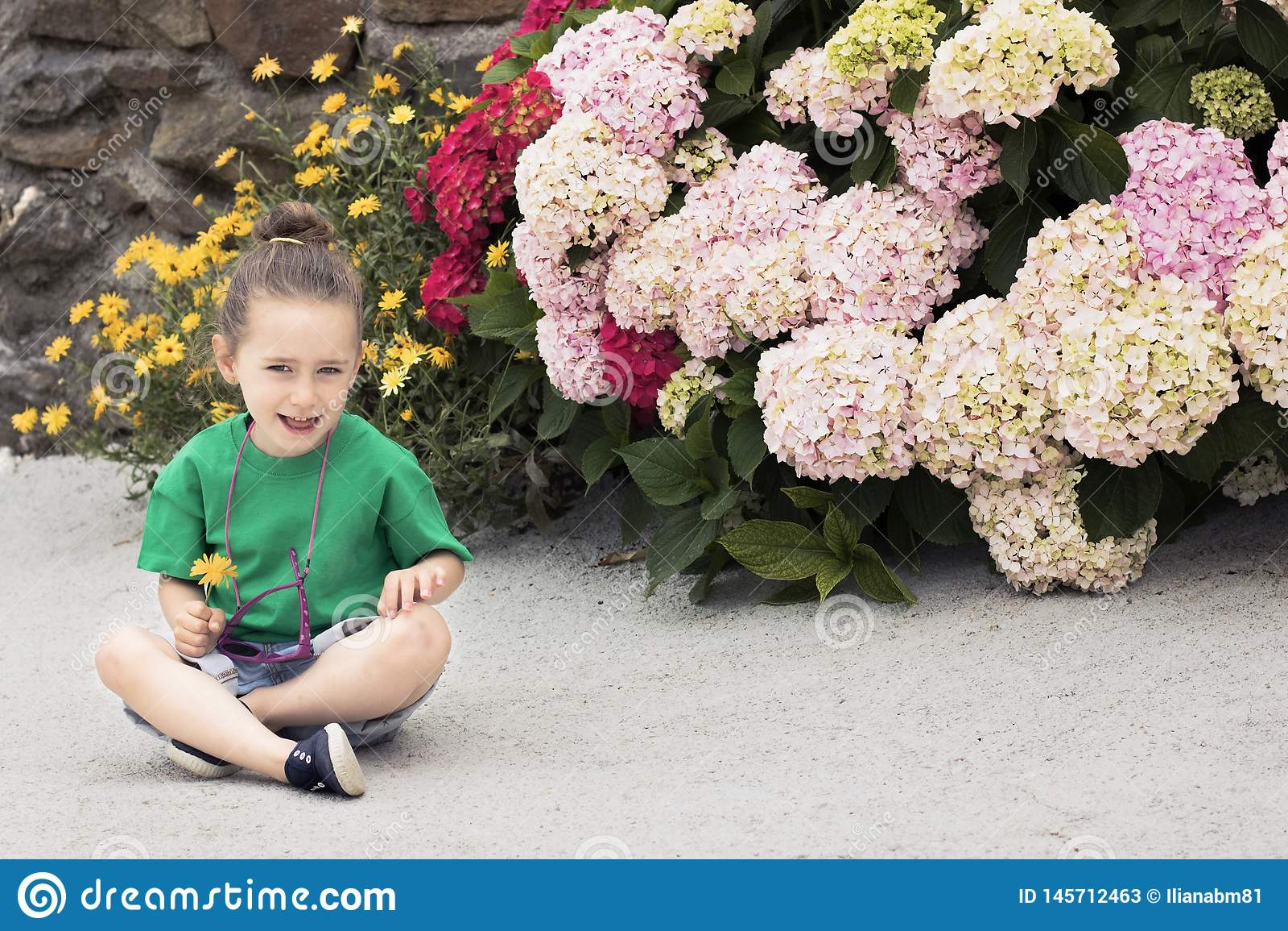 Ένα 4χρονο κορίτσι κρατά ένα marigold λουλούδι