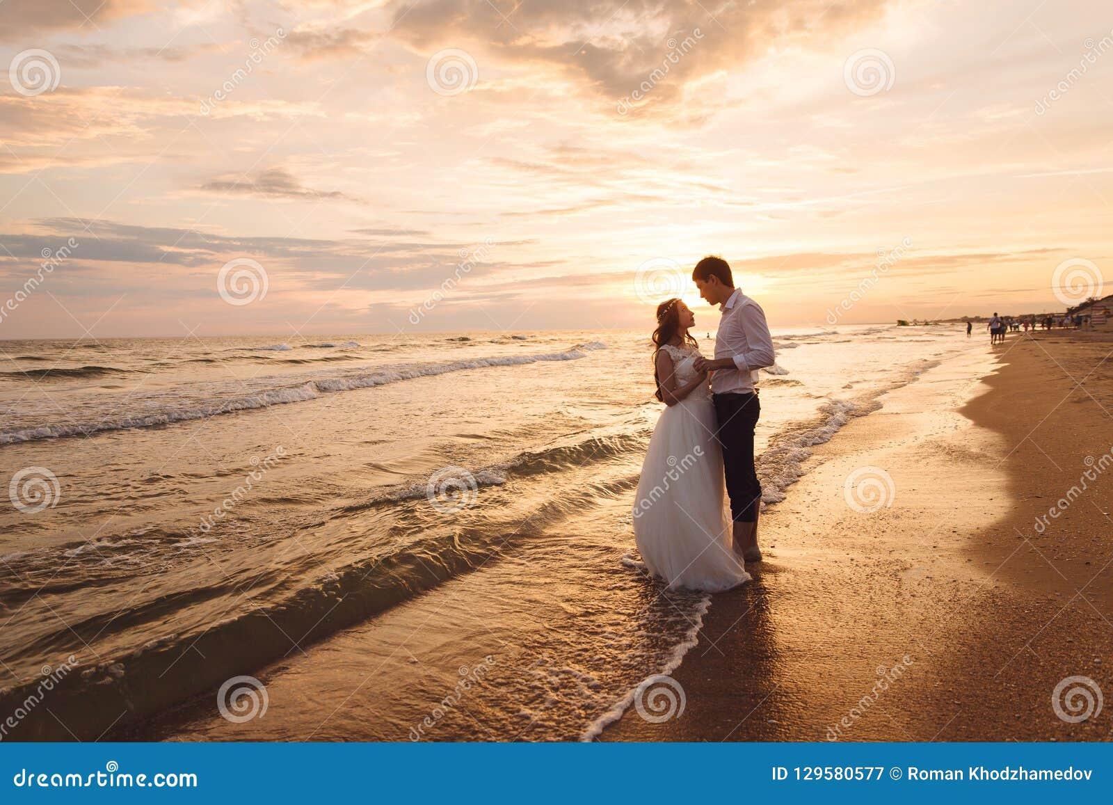Ένα όμορφο ζεύγος των newlyweds, η νύφη και ο νεόνυμφος που περπατούν στην παραλία Πανέμορφο ηλιοβασίλεμα και ουρανός Γαμήλια φορ