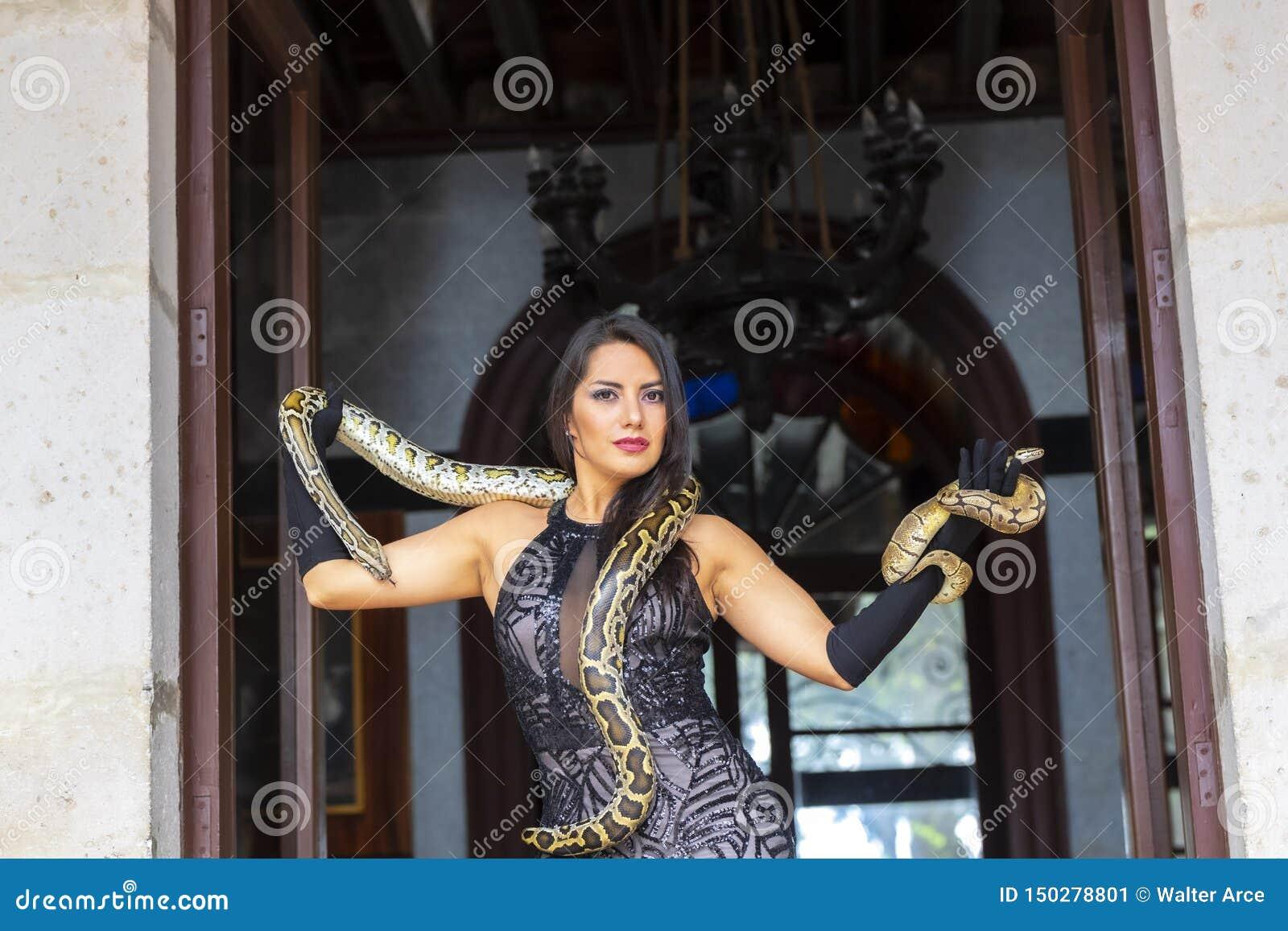 Ένα όμορφο ισπανικό πρότυπο Brunette θέτει με ένα Boa φίδι σφιγκτήρων γύρω από το σώμα της