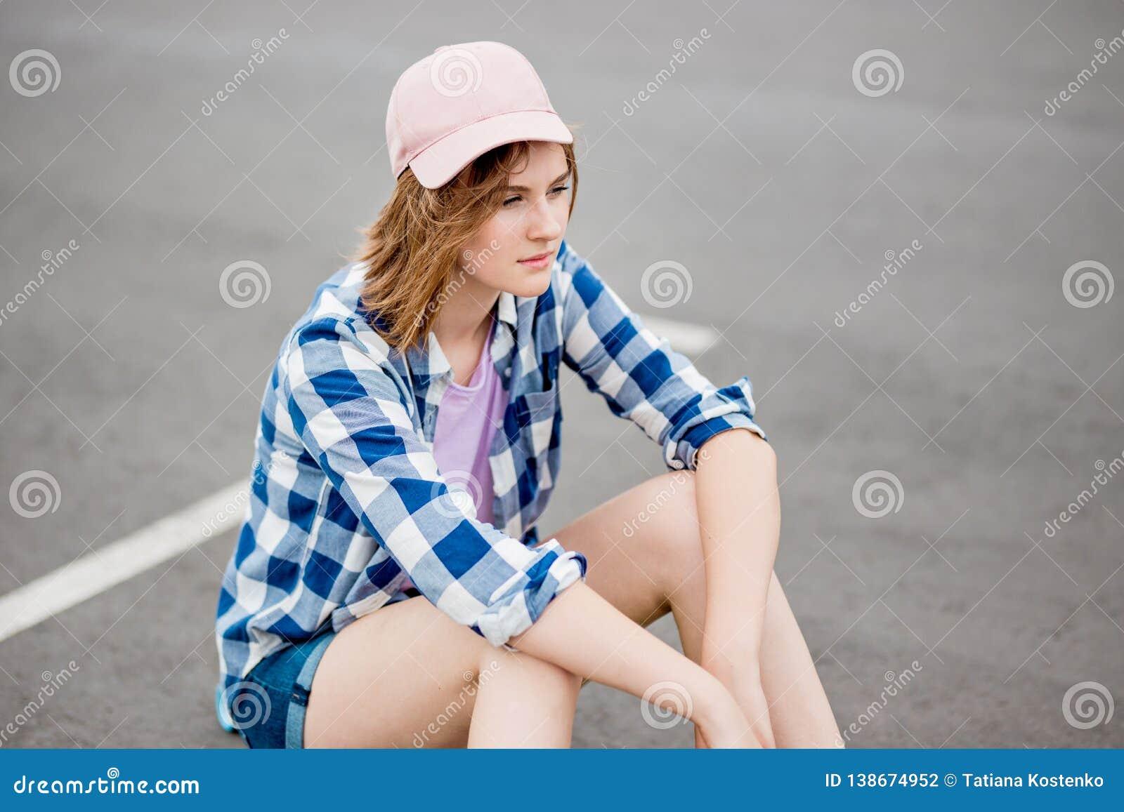 Ένα όμορφο ξανθό κορίτσι που φορά τα ελεγμένα σορτς πουκάμισων, ΚΑΠ και τζιν κάθεται στο υπαίθριο σταθμό αυτοκινήτων με ένα στοχα