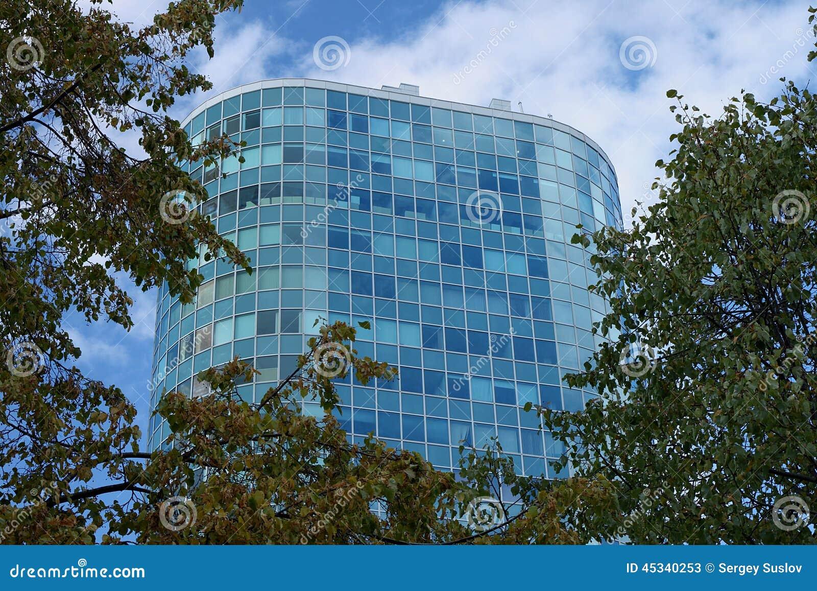 Ένα όμορφο υψηλό μπλε κτίριο γραφείων γυαλιού που περιβάλλεται από τα δέντρα