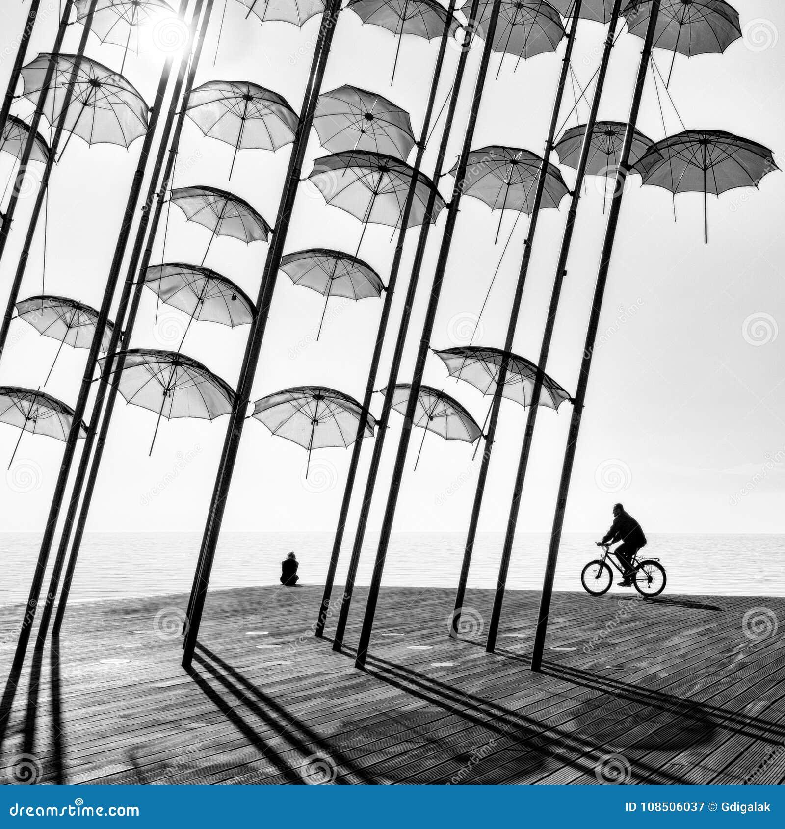 Ένα bicyclist και ένα κορίτσι κάτω από τις ομπρέλες