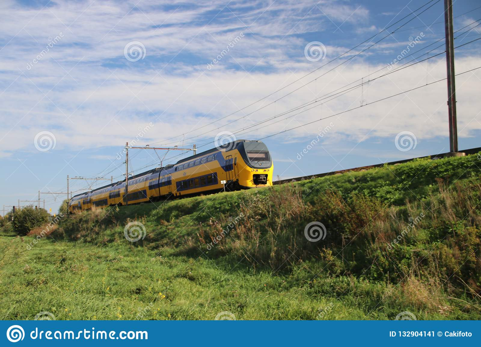Ένα intercity τραίνο VIRM στη διαδρομή σιδηροδρόμου sealevel στο κρησφύγετο IJssel Nieuwerkerk aan