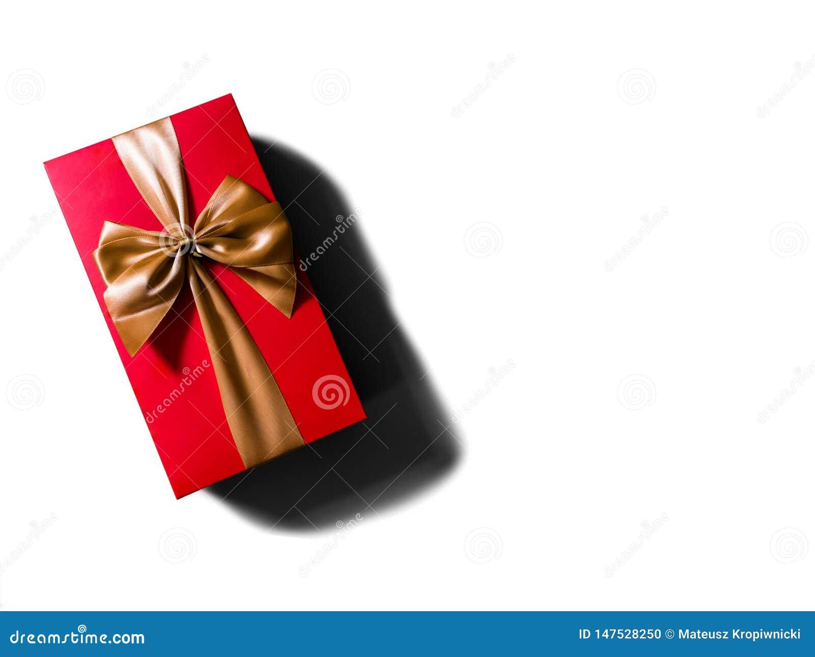 Έννοια ή ιδέα της επίπεδης άποψης του κόκκινου κιβωτίου δώρων με τη χρυσό κορδέλλα ή το τόξο