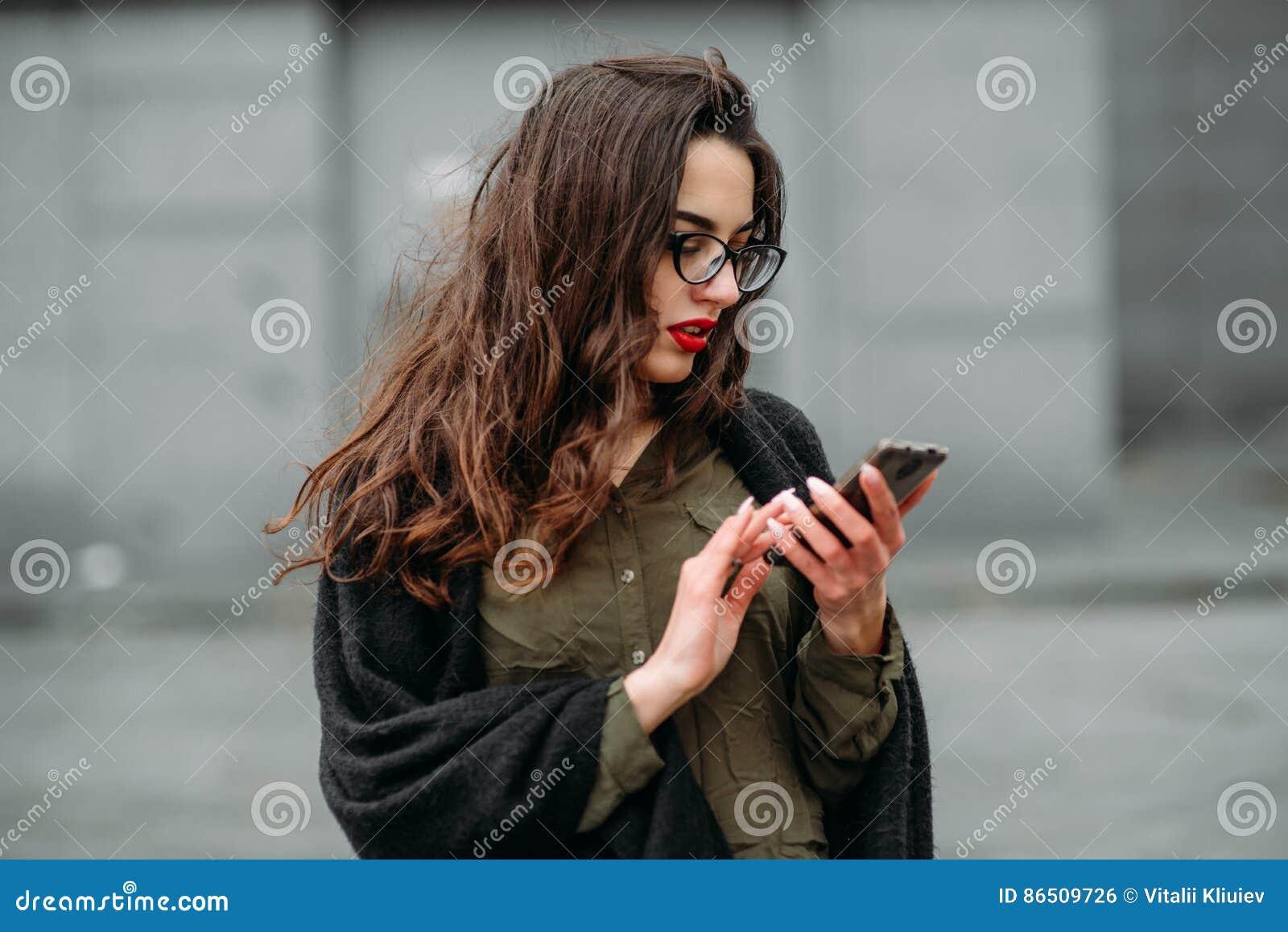 Έννοια μόδας: όμορφο νέο κορίτσι με μακρυμάλλη, τα γυαλιά, κόκκινα χείλια που στέκεται κοντά στο σύγχρονο τοίχο που φορά στο πράσ