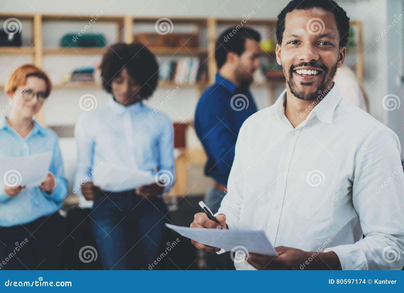 Έννοια ομαδικής εργασίας στο σύγχρονο γραφείο Νέος αφρικανικός επιχειρηματίας που φορά τα άσπρα έγγραφα εκμετάλλευσης πουκάμισων