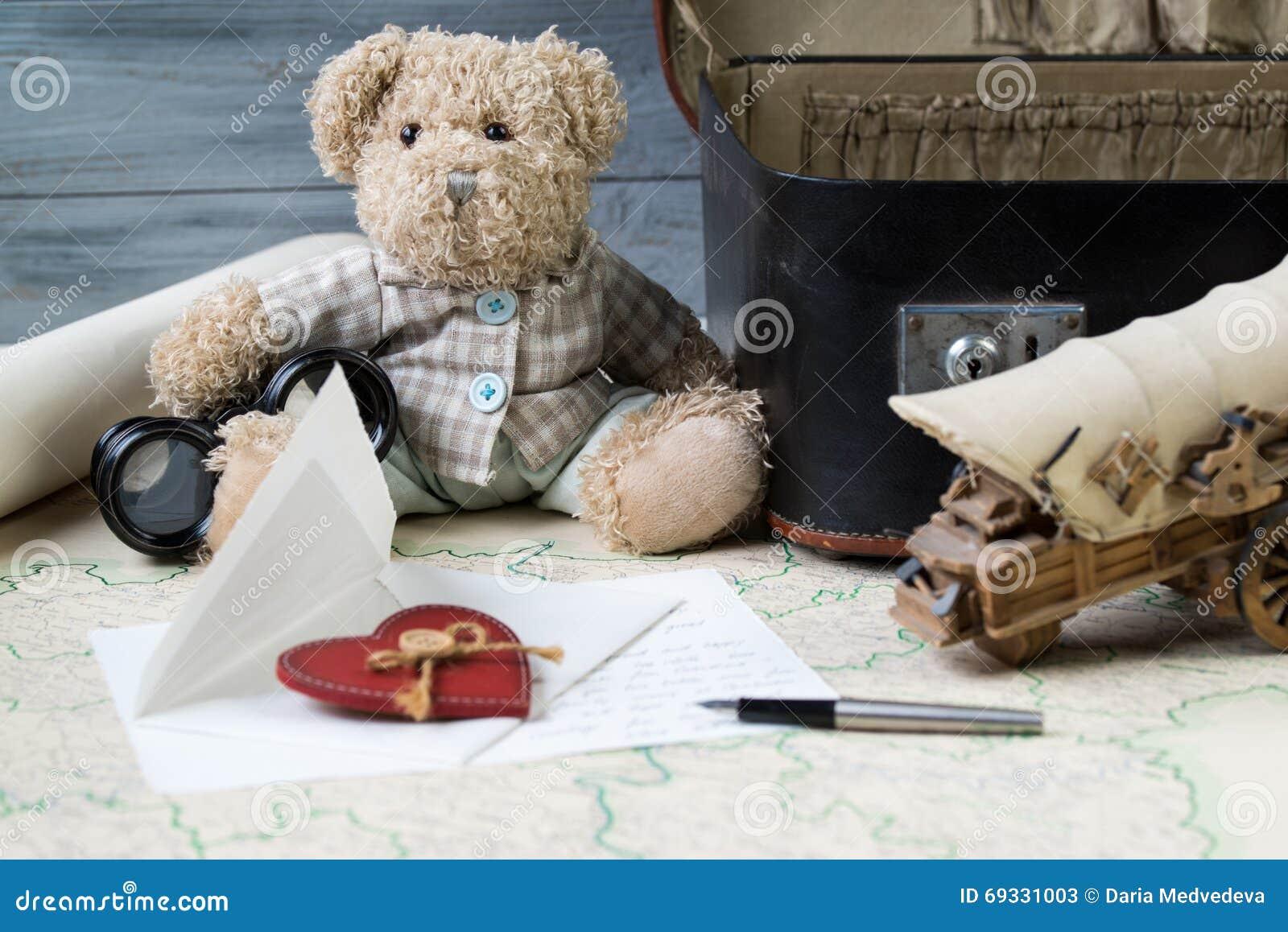 Έννοια ταξιδιού, teddy αρκούδα με τις παλαιές διόπτρες και βαλίτσα στον παλαιό χάρτη με την επιστολή και μια μάνδρα πηγών