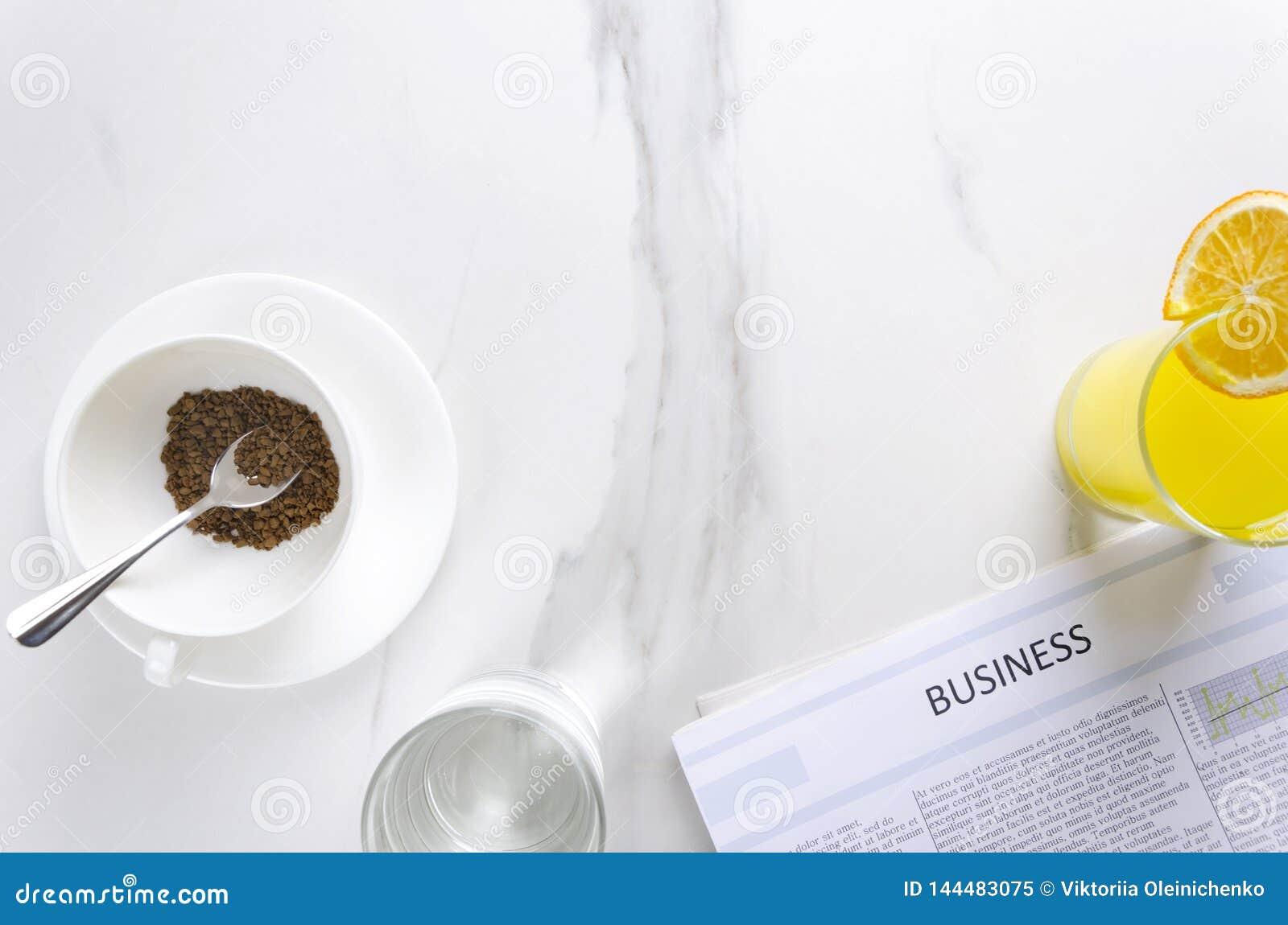 Έννοια του επιχειρησιακού πρωινού στο γραφείο Φλιτζάνι του καφέ, γυαλί του wate, χυμός από πορτοκάλι και φρέσκια εφημερίδα διάστη