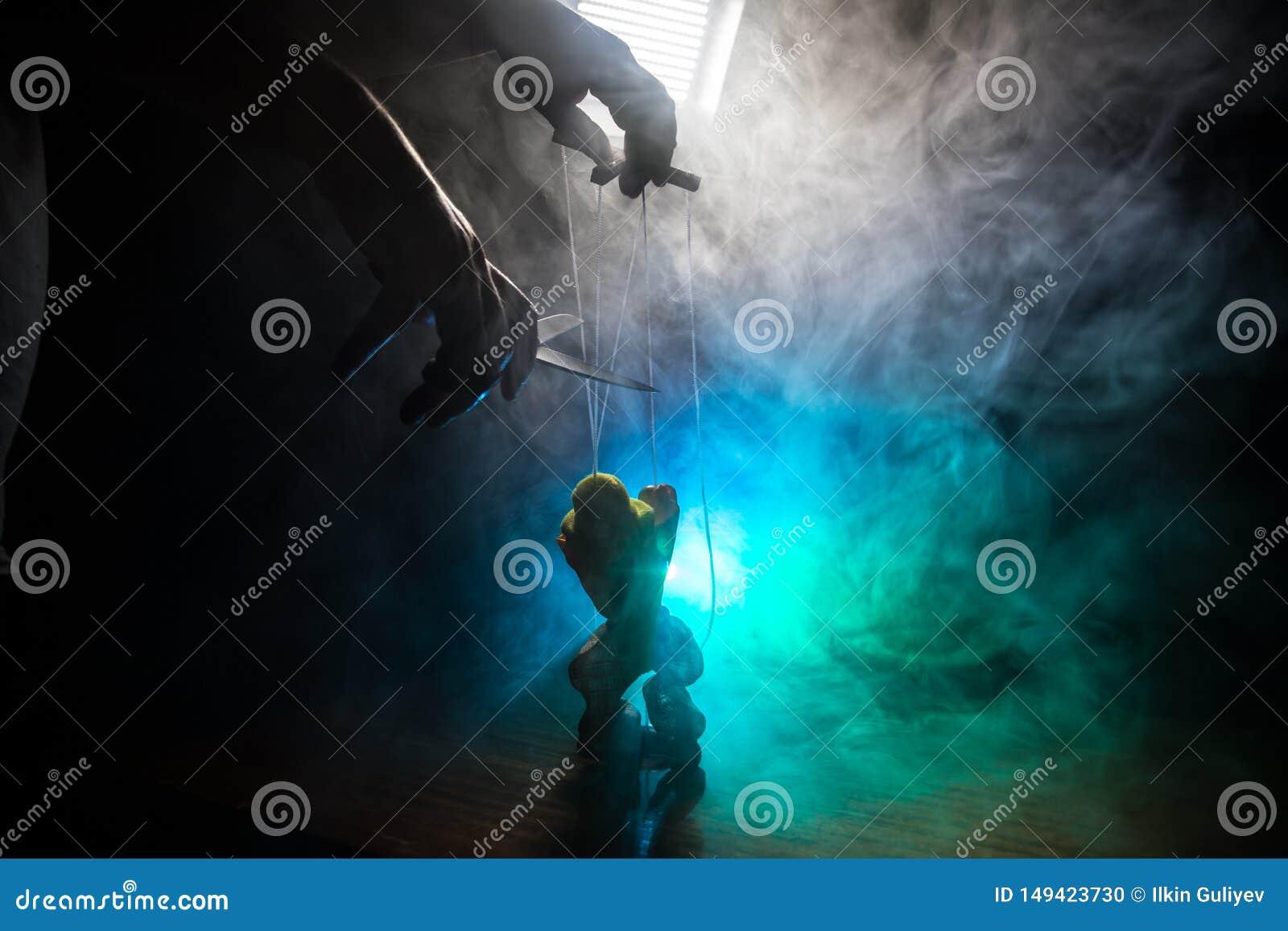 Έννοια του χειρισμού Το χέρι κρατά τις σειρές για το χειρισμό Το χέρι ελέγχει τις σειρές μαριονετών σε ένα σκοτεινό ομιχλώδες υπό