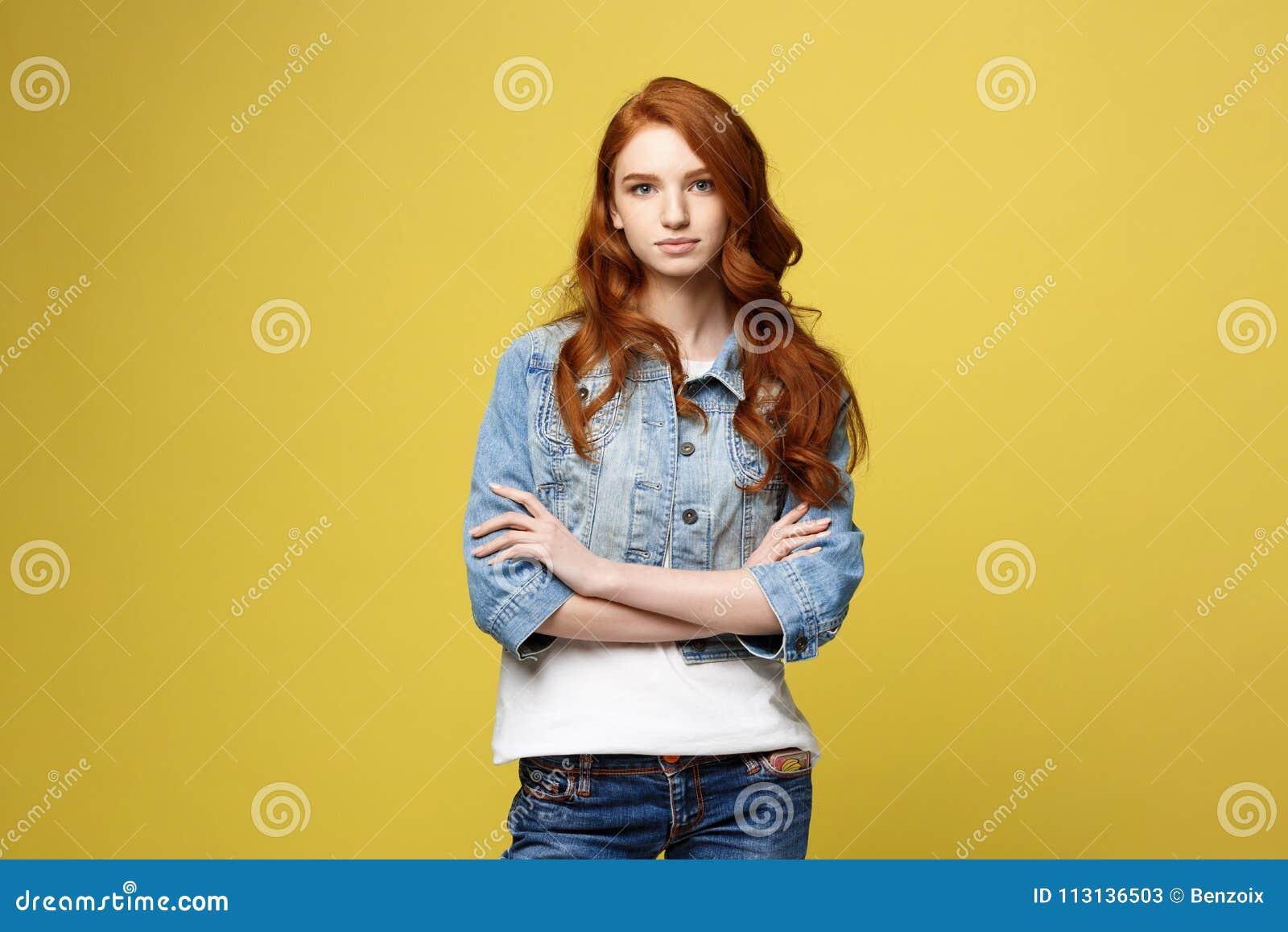 Έννοια τρόπου ζωής: Η νέα καυκάσια όμορφη γυναίκα στο σακάκι τζιν διέσχισε τα όπλα - που απομονώθηκαν πέρα από το φωτεινό κίτρινο