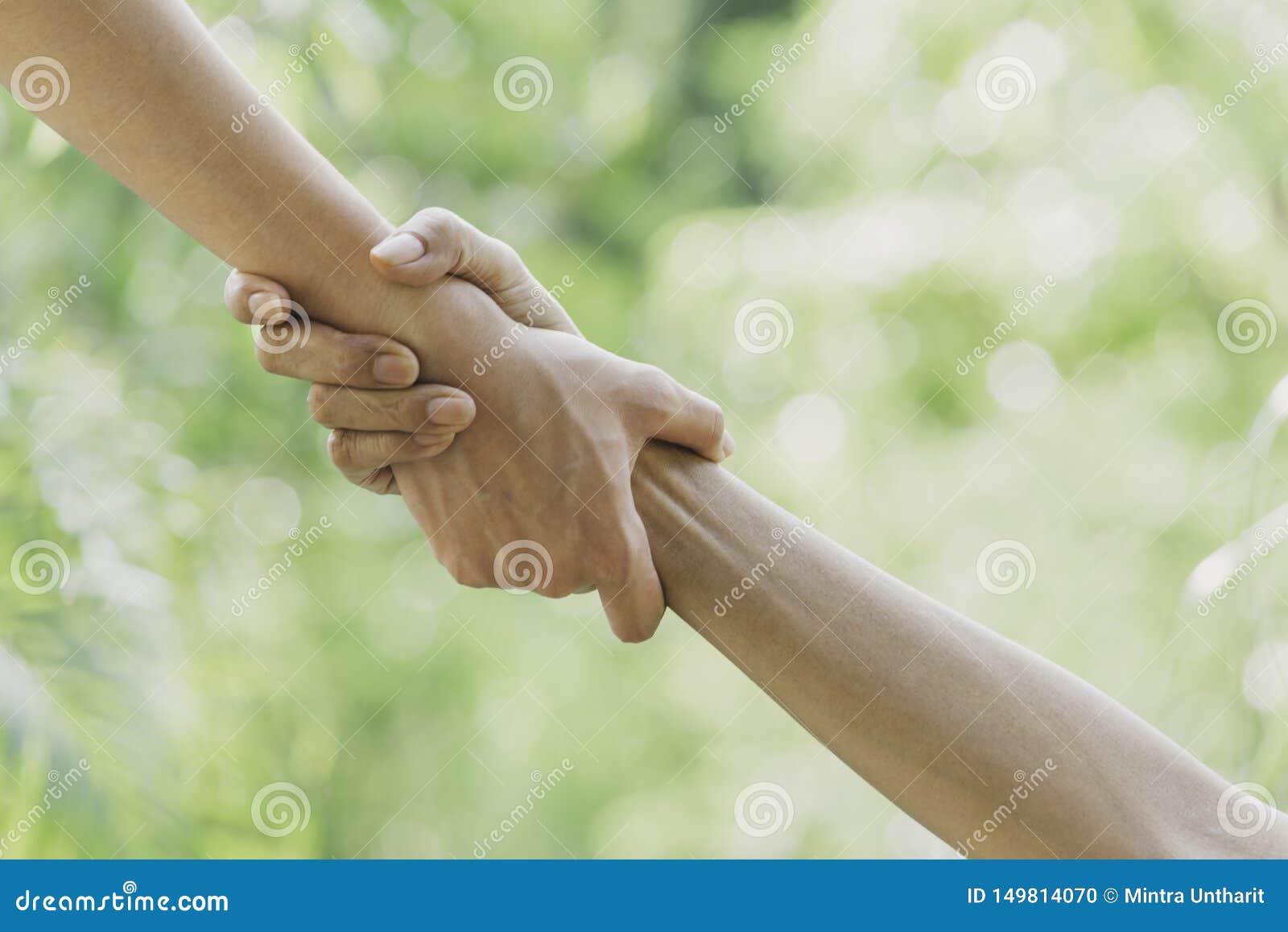 Έννοια χεριών βοηθείας Εκμετάλλευση χεριών για τη βοήθεια στο υπόβαθρο φύσης