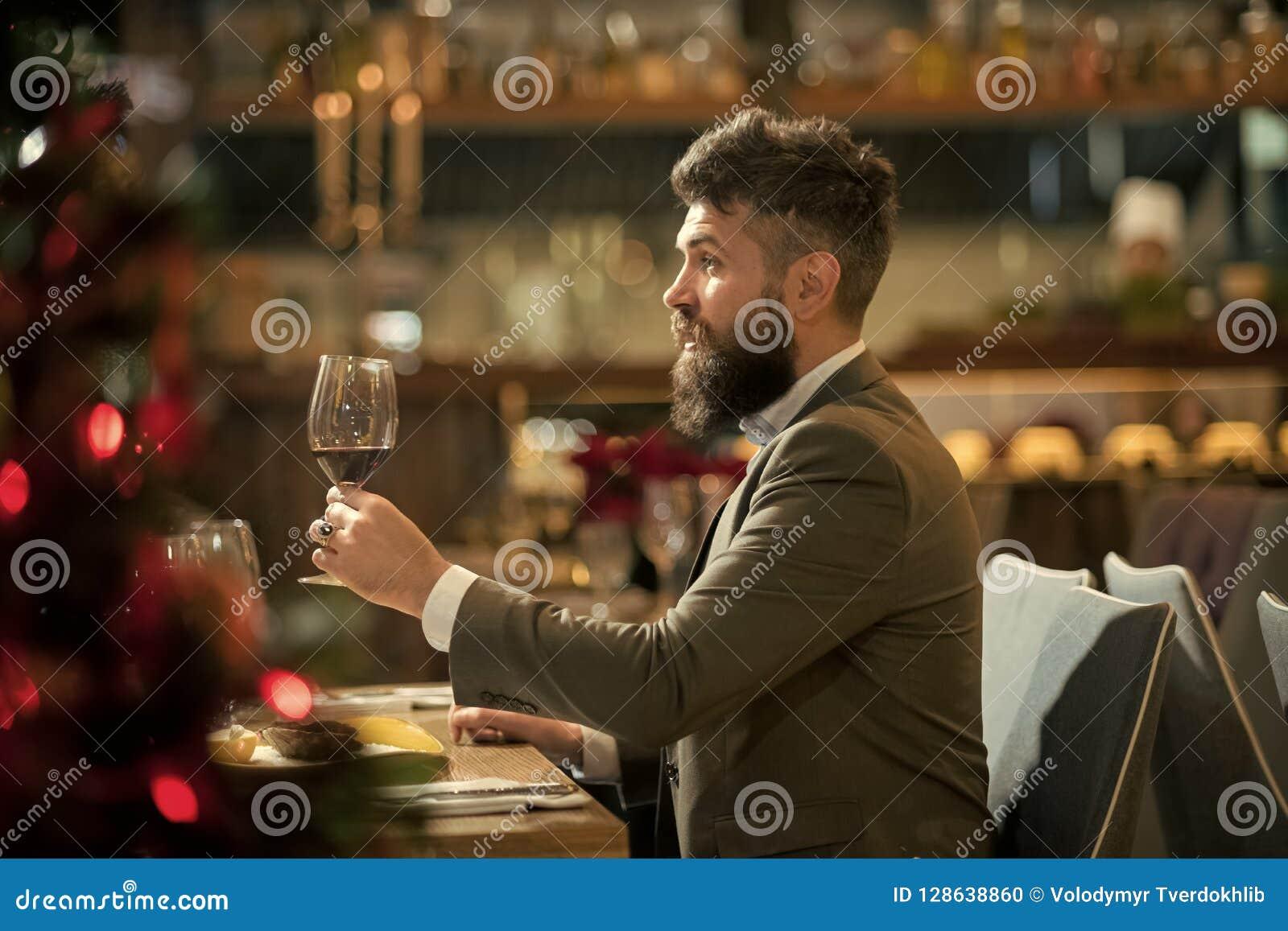 Έξοδα του μεγάλου χρόνου στο εστιατόριο Όμορφο γυαλί εκμετάλλευσης νεαρών άνδρων με το κόκκινο κρασί και χαμόγελο στο εστιατόριο