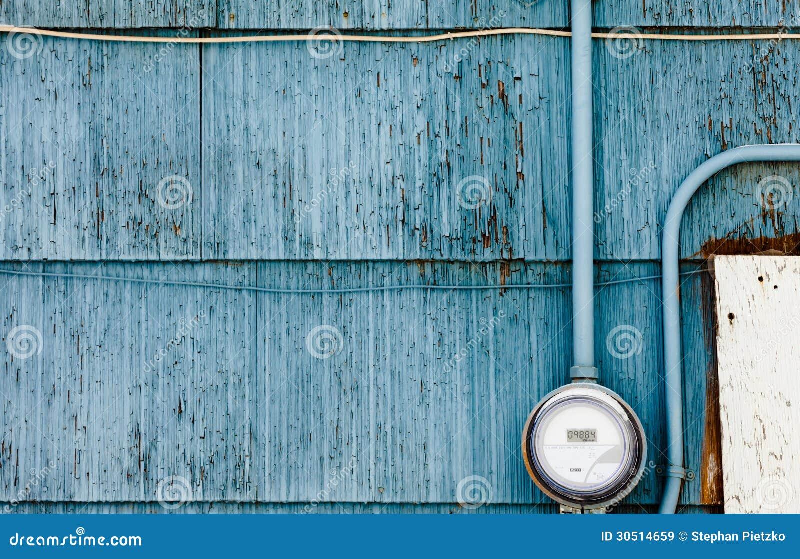 Έξυπνος μετρητής παροχής ηλεκτρικού ρεύματος πλέγματος στο βρώμικο μπλε τοίχο
