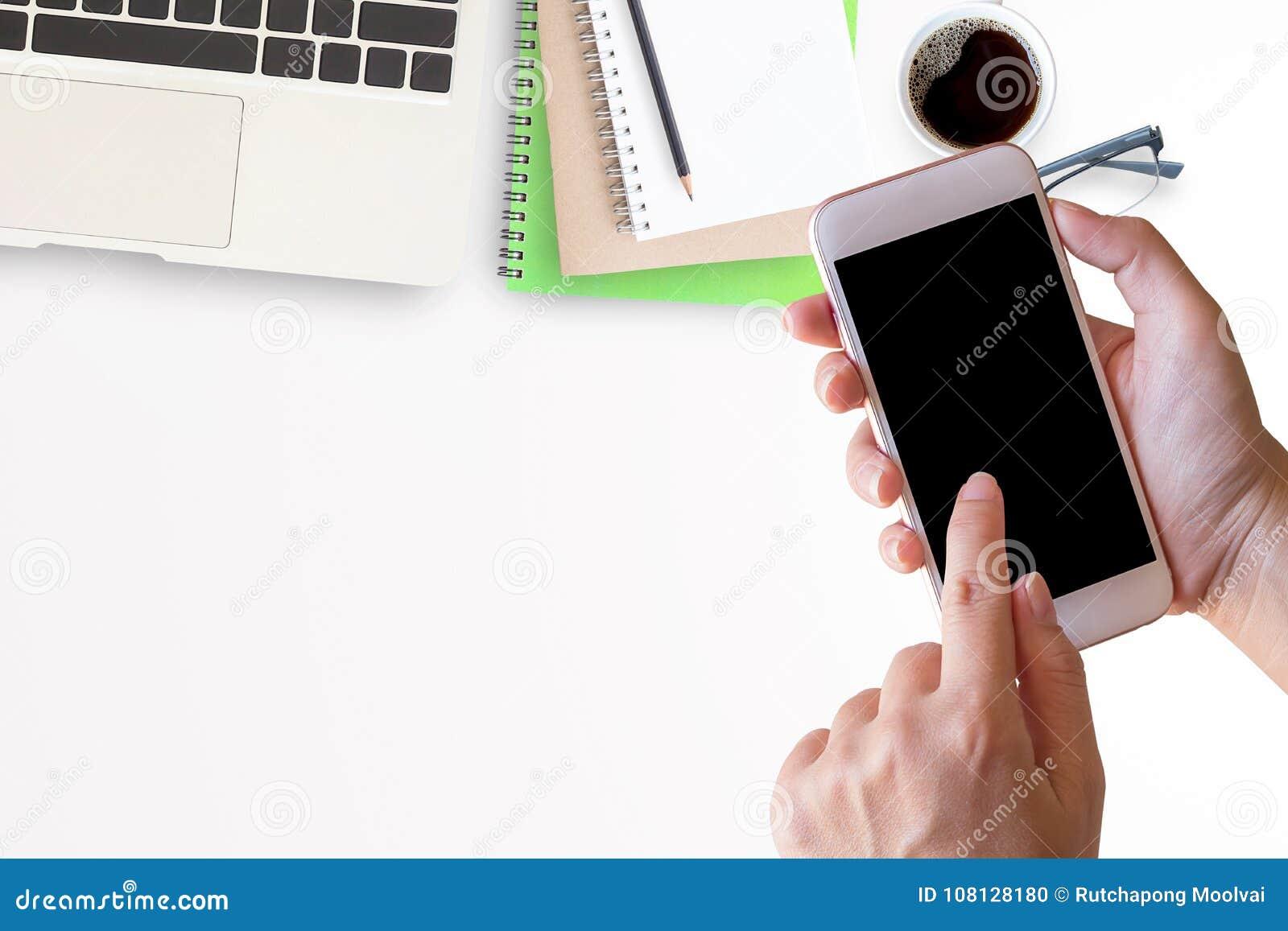 Έξυπνο τηλέφωνο στο θηλυκό χέρι με το γραφείο γραφείων με το lap-top