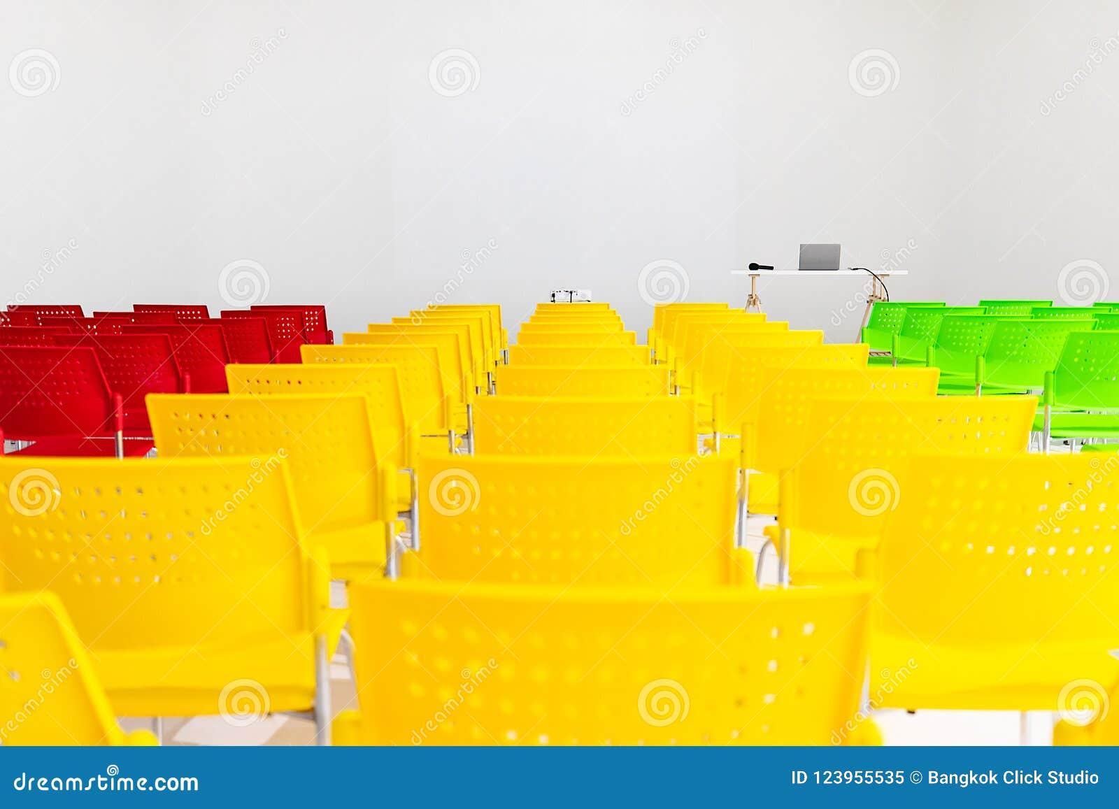 Έτοιμος να χρησιμοποιήσει τις σειρές των ζωηρόχρωμων καρεκλών στη αίθουσα συνδιαλέξεων με υπέρ