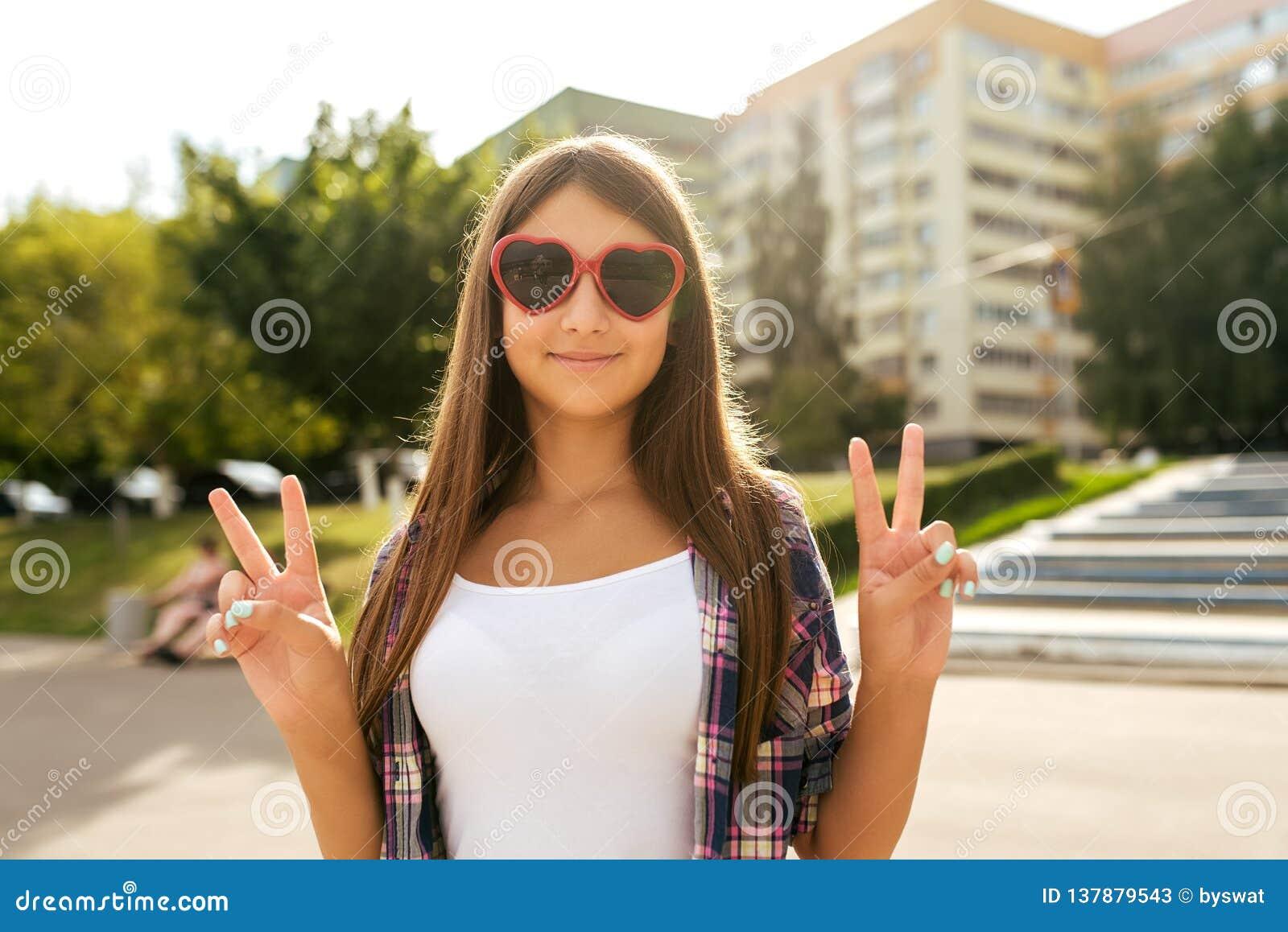 cdcf7ec8d14 Έφηβος 9-13 κοριτσιών χρονών, που στέκεται το καλοκαίρι στο πάρκο πόλεων,  νίκη χειρονομίας χεριών γειά σου Το καλοκαίρι, ευτυχή χαμόγελα Η έννοια της  ...
