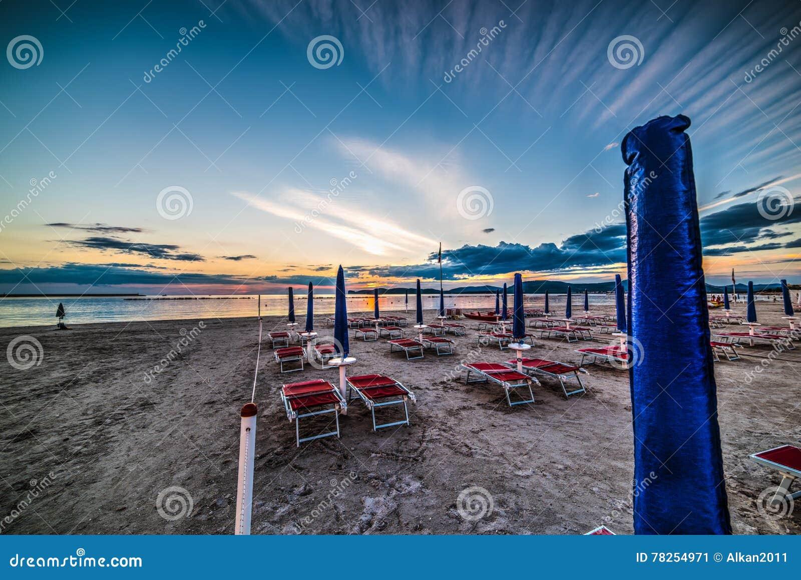 Έδρες και parasol θαλασσίως στο ηλιοβασίλεμα