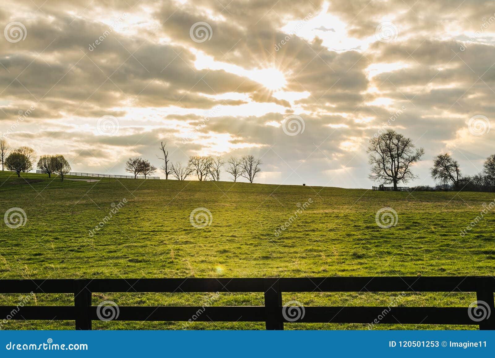 Ήλιος που λάμπει μέσω των σύννεφων πέρα από έναν πράσινο τομέα σε αργά το απόγευμα