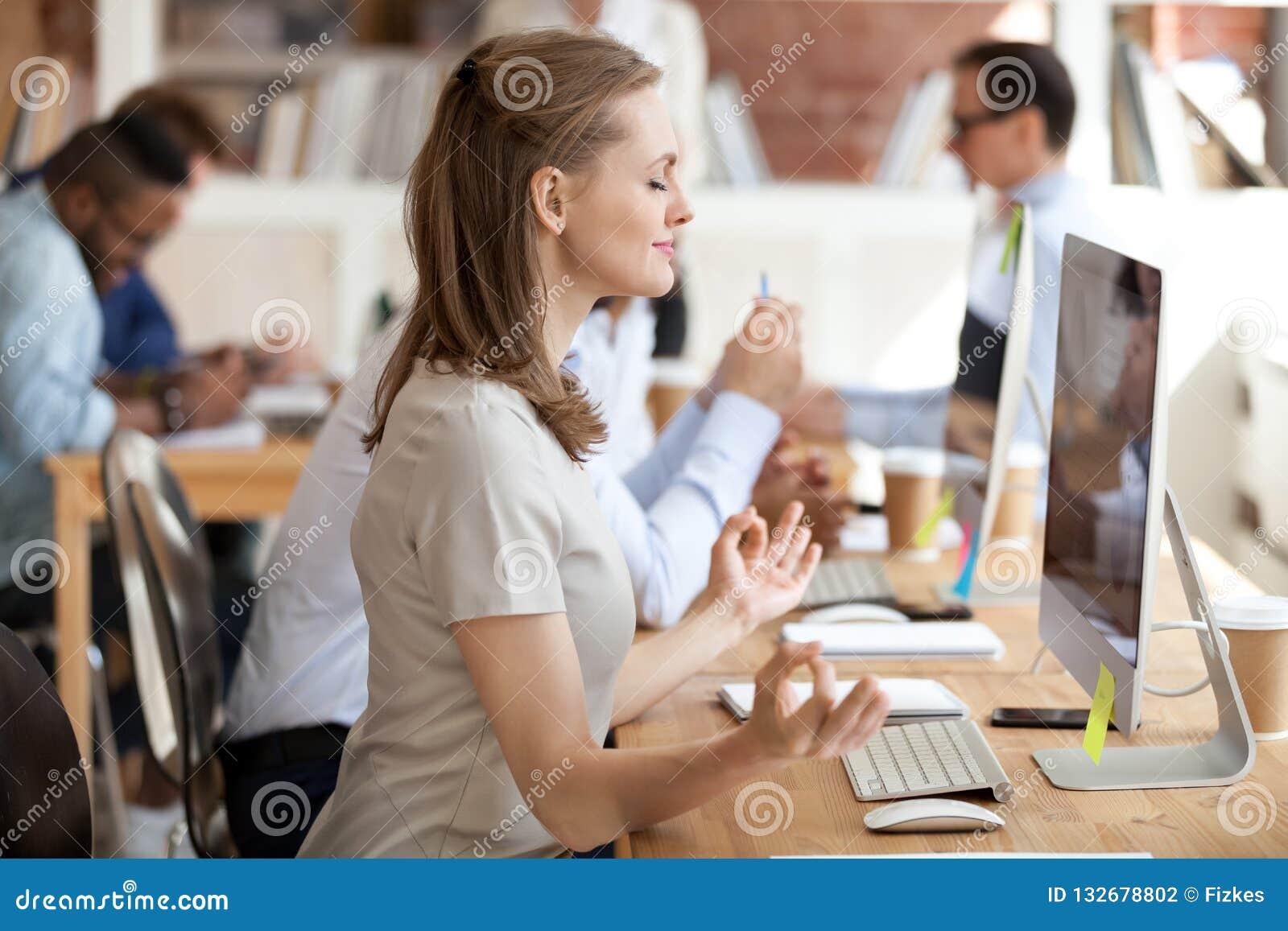 Ήρεμη επιχειρηματίας που κάνει την άσκηση γιόγκας στον εργασιακό χώρο