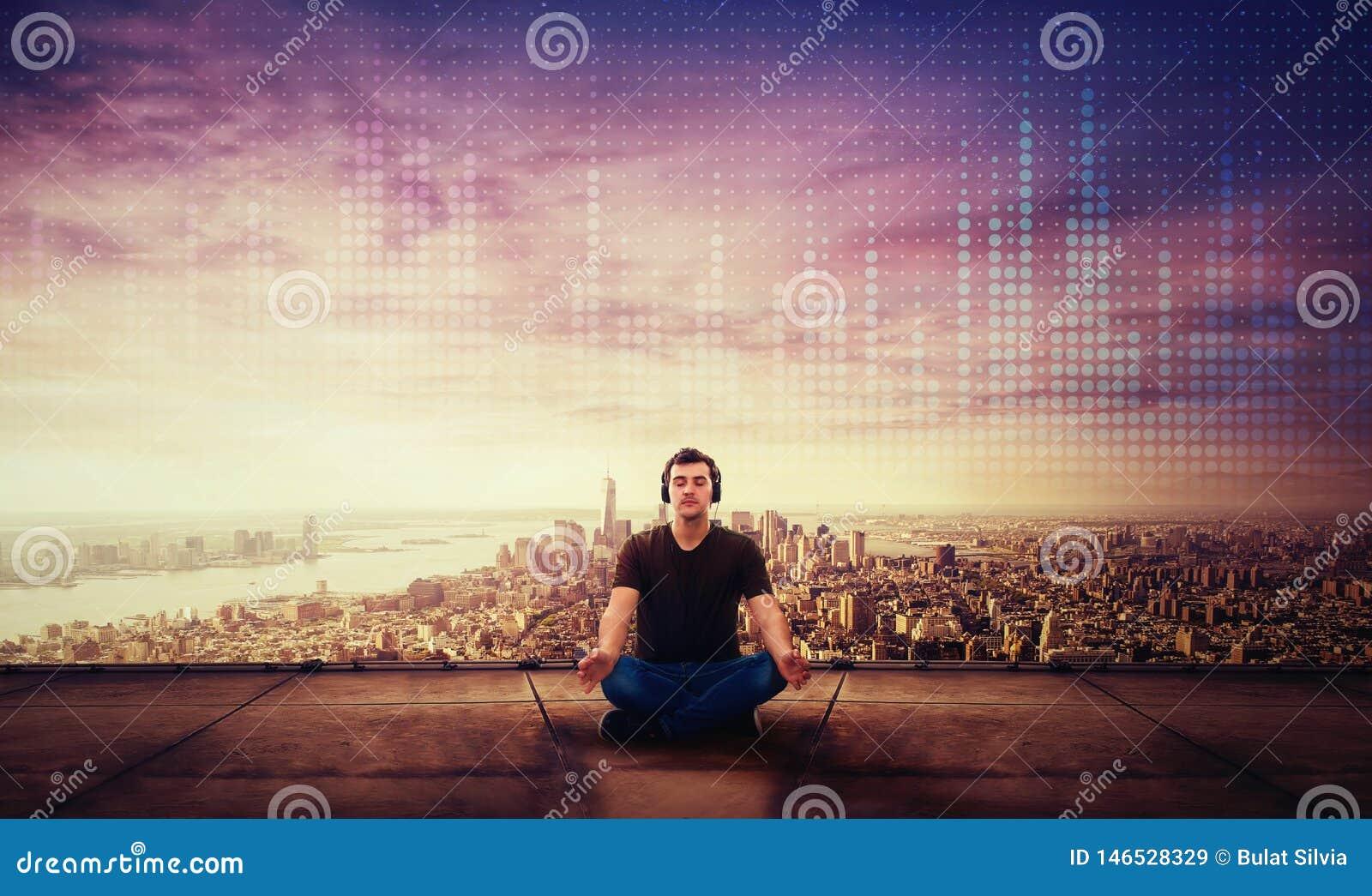 Ήρεμη συνεδρίαση τύπων στη στέγη ενός ουρανοξύστη meditate στο ηλιοβασίλεμα πέρα από τον ορίζοντα πόλεων