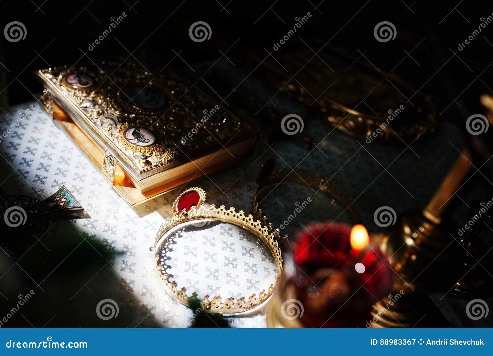 Ήλιος που λάμπει στο Ευαγγέλιο και τις κορώνες Βίβλων στην εκκλησία στη  γαμήλια τελετή Έννοια θρησκείας πίστης 5b9cf93dd0d