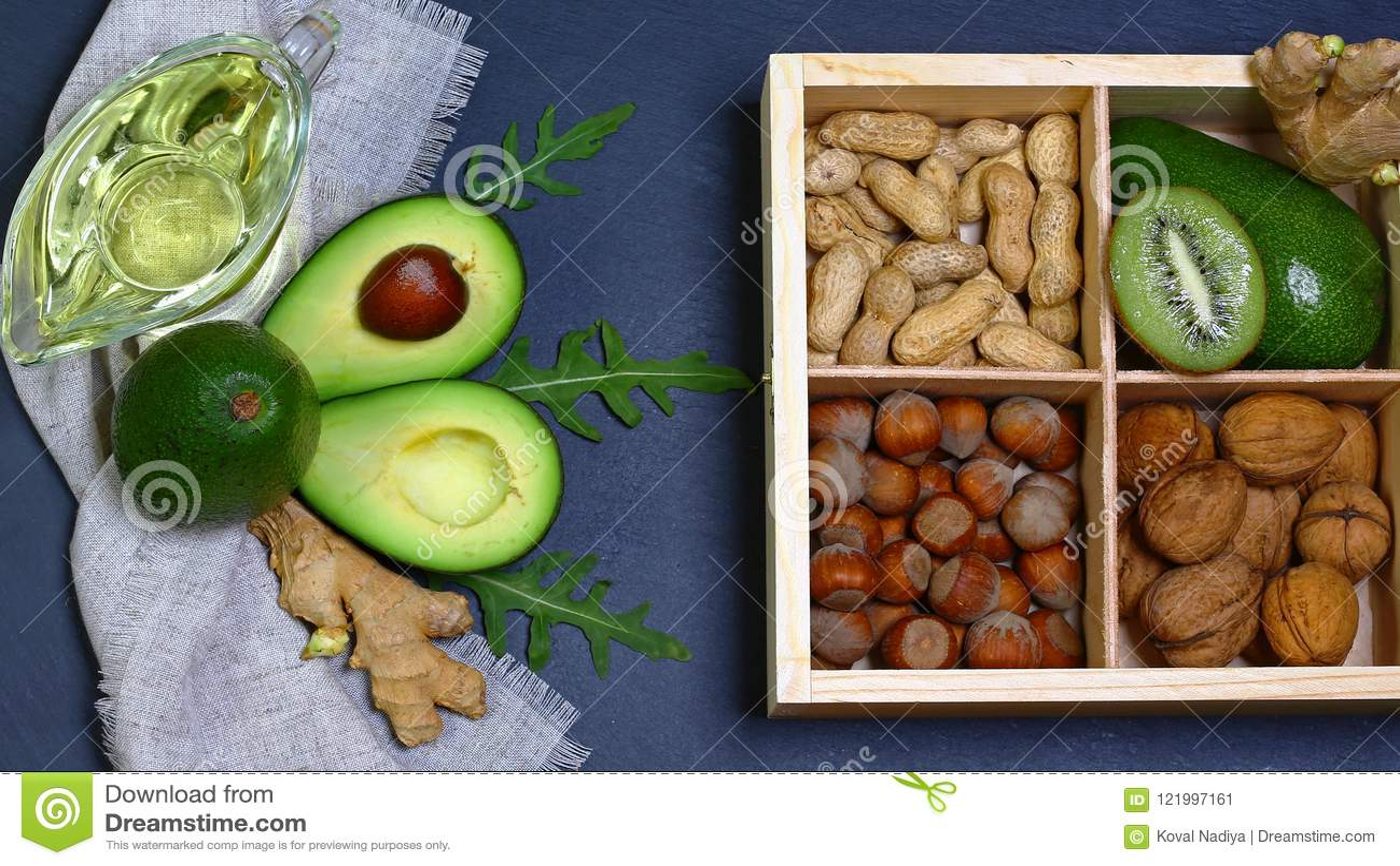 Αβοκάντο, ακτινίδιο, ξύλα καρυδιάς και αμύγδαλα, ελαιόλαδο στον πίνακα σχιστόλιθου - τρόφιμα πλούσια σε καλά πετρέλαια Επίπεδος β