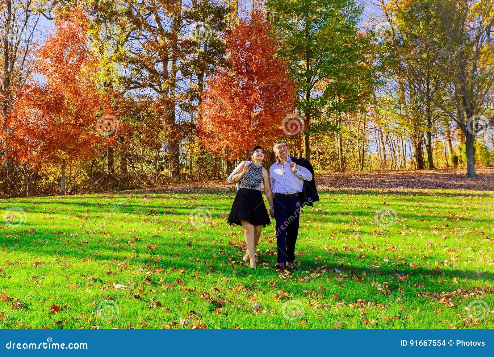 αγάπη, σχέσεις, ευτυχές νέο ζεύγος εποχής και έννοιας ανθρώπων που αγκαλιάζει στο πάρκο φθινοπώρου