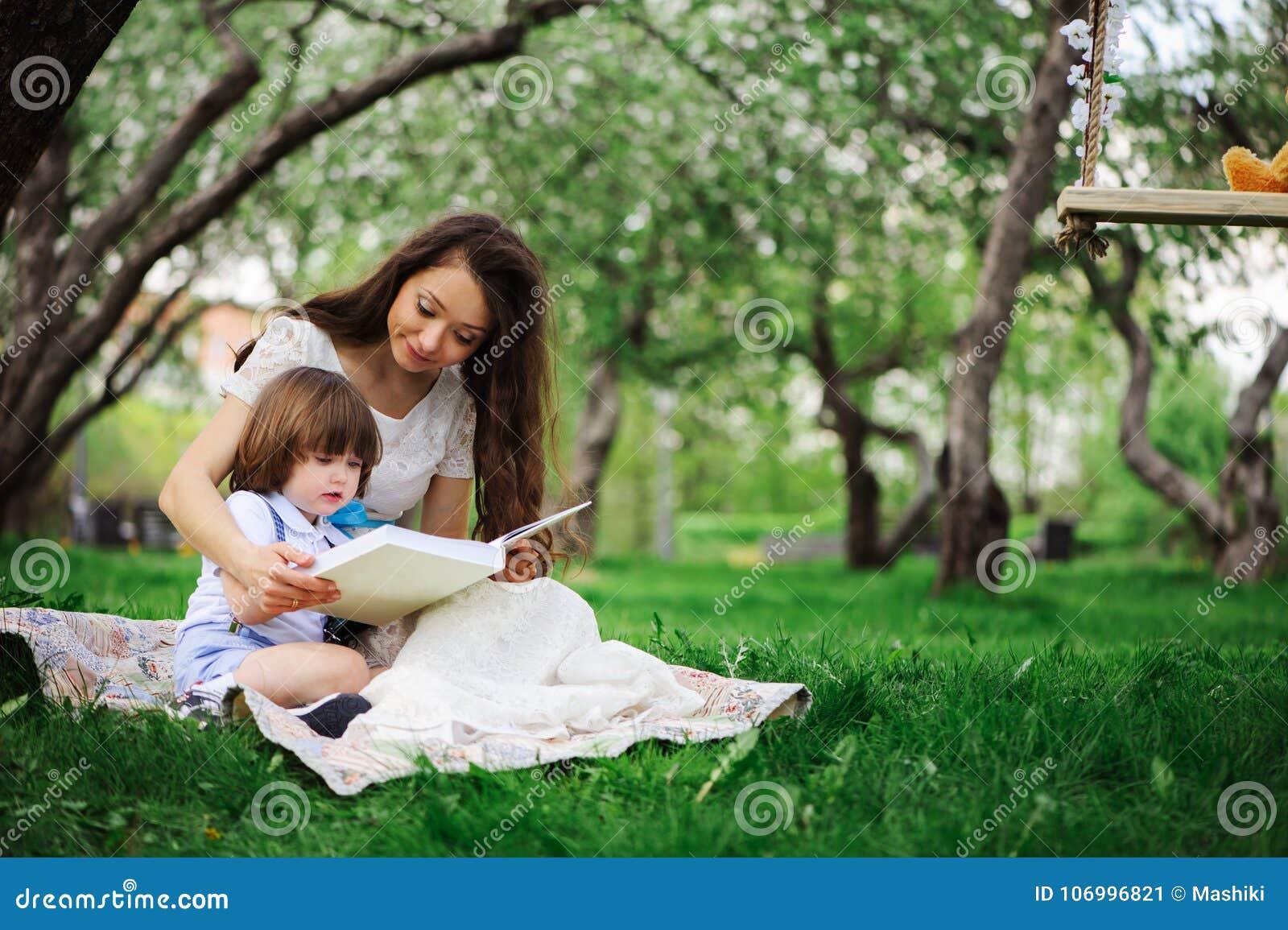 αγαπώντας το βιβλίο ανάγνωσης μητέρων στο γιο μικρών παιδιών υπαίθριο στο πικ-νίκ την άνοιξη ή το θερινό πάρκο Ευτυχής ημέρα οικο