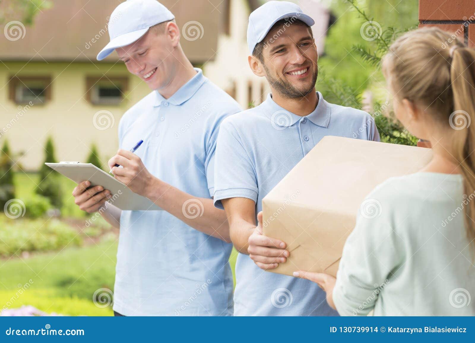 Αγγελιαφόροι στις μπλε στολές και καλύμματα που δίνουν τη συσκευασία σε έναν πελάτη