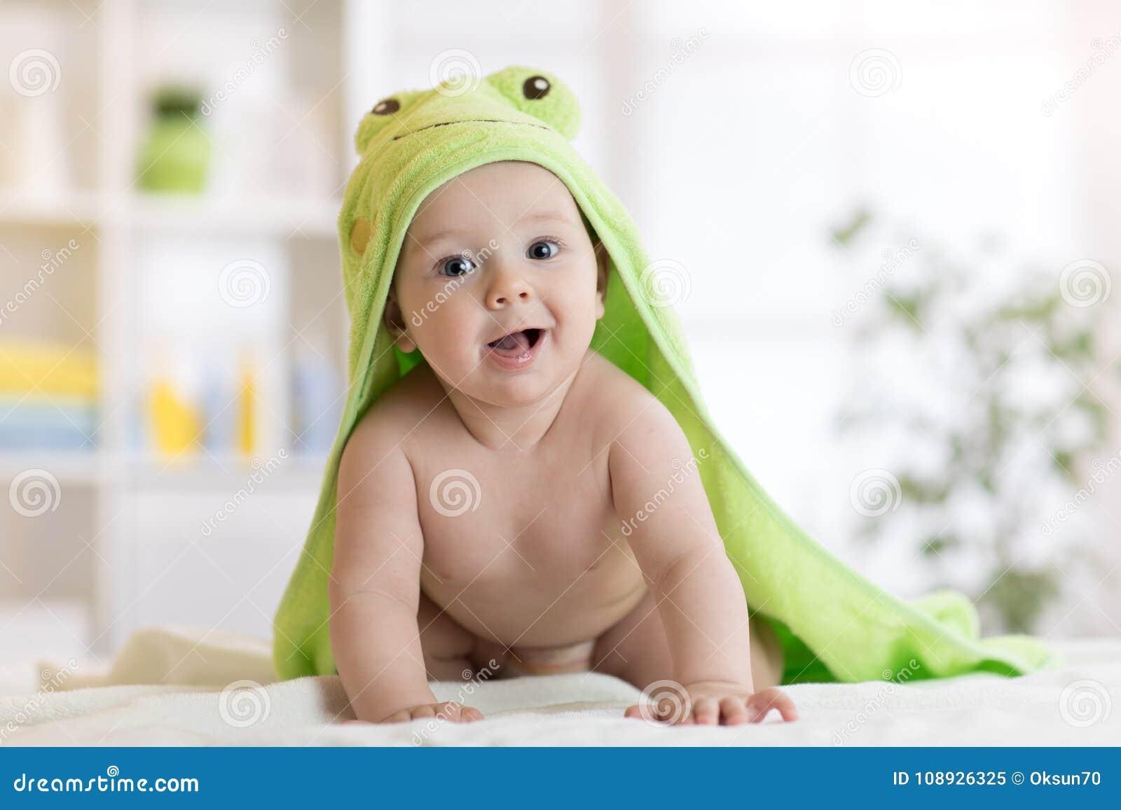 Αγοράκι που φορά την πράσινη πετσέτα στην ηλιόλουστη κρεβατοκάμαρα Νεογέννητη χαλάρωση παιδιών μετά από το λουτρό ή το ντους
