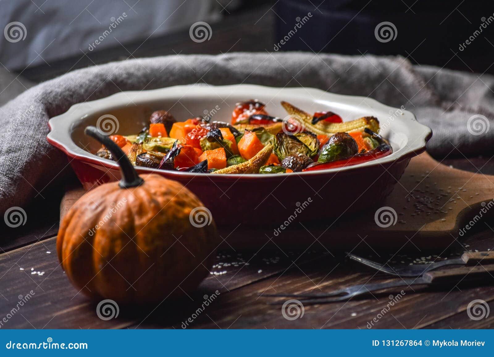 Αγροτική ακόμα ζωή των ψημένων στη σχάρα λαχανικών και σε ένα μεγάλο κεραμικό πιάτο και τις συσκευές σε ένα ξύλινο υπόβαθρο διάστ
