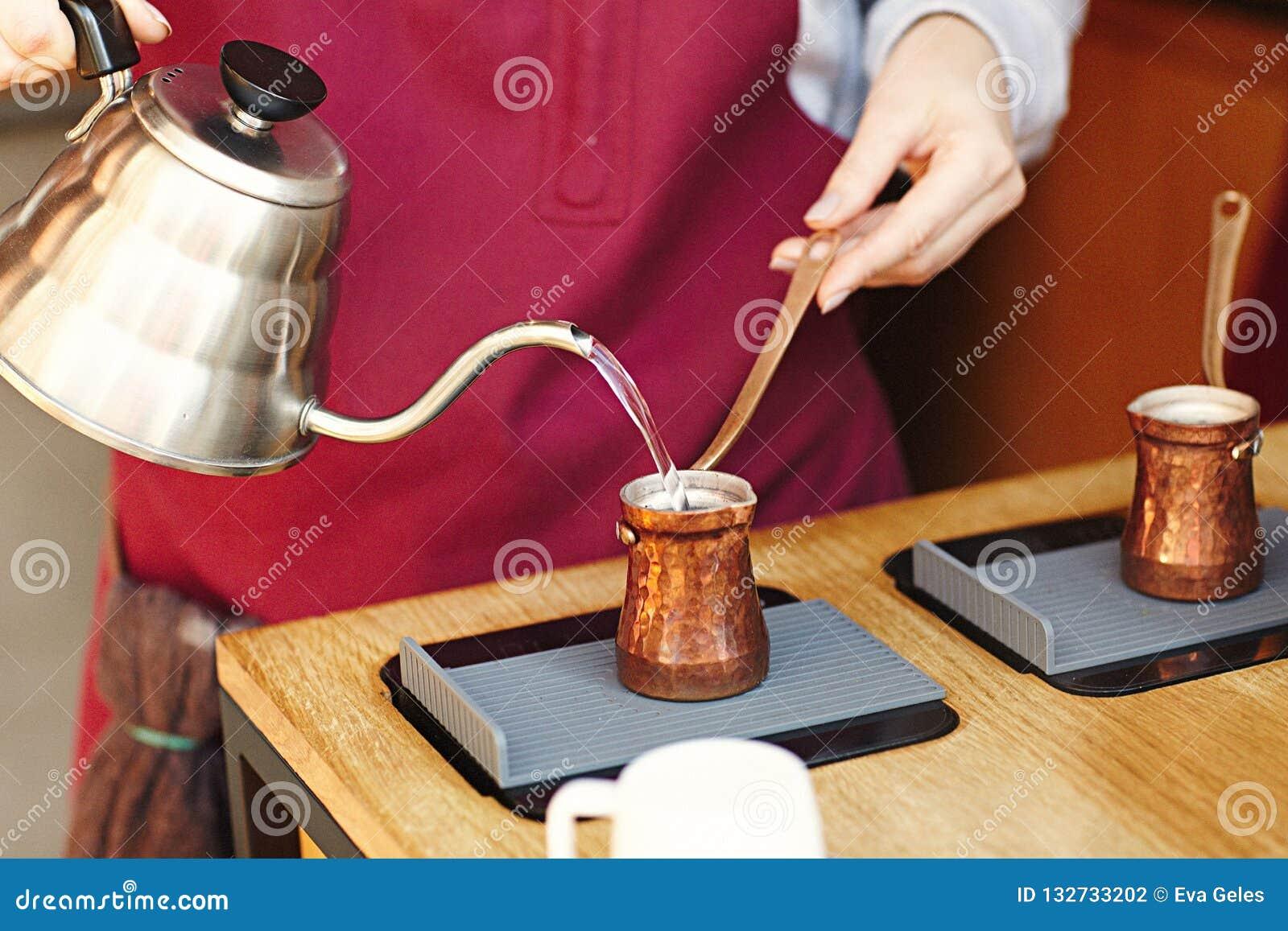 Αγροτικό τουρκικό cezve, καφετιέρα, ibrik με τα βρασμένα φασόλια καφέ, το νερό, τα καρυκεύματα, την κανέλα, το άλας στην ηλεκτρικ