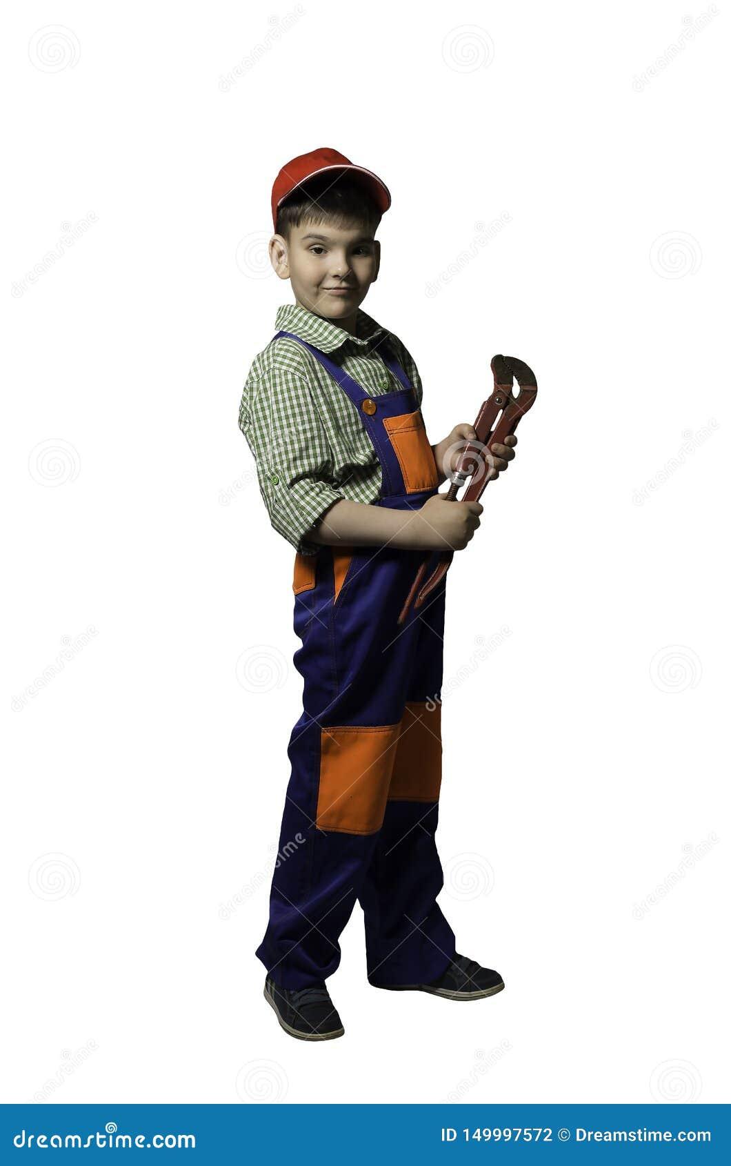 Αγόρι, έφηβος με τα εργαλεία για την επισκευή και κατασκευή, στις φόρμες και το κράνος, που απομονώνονται
