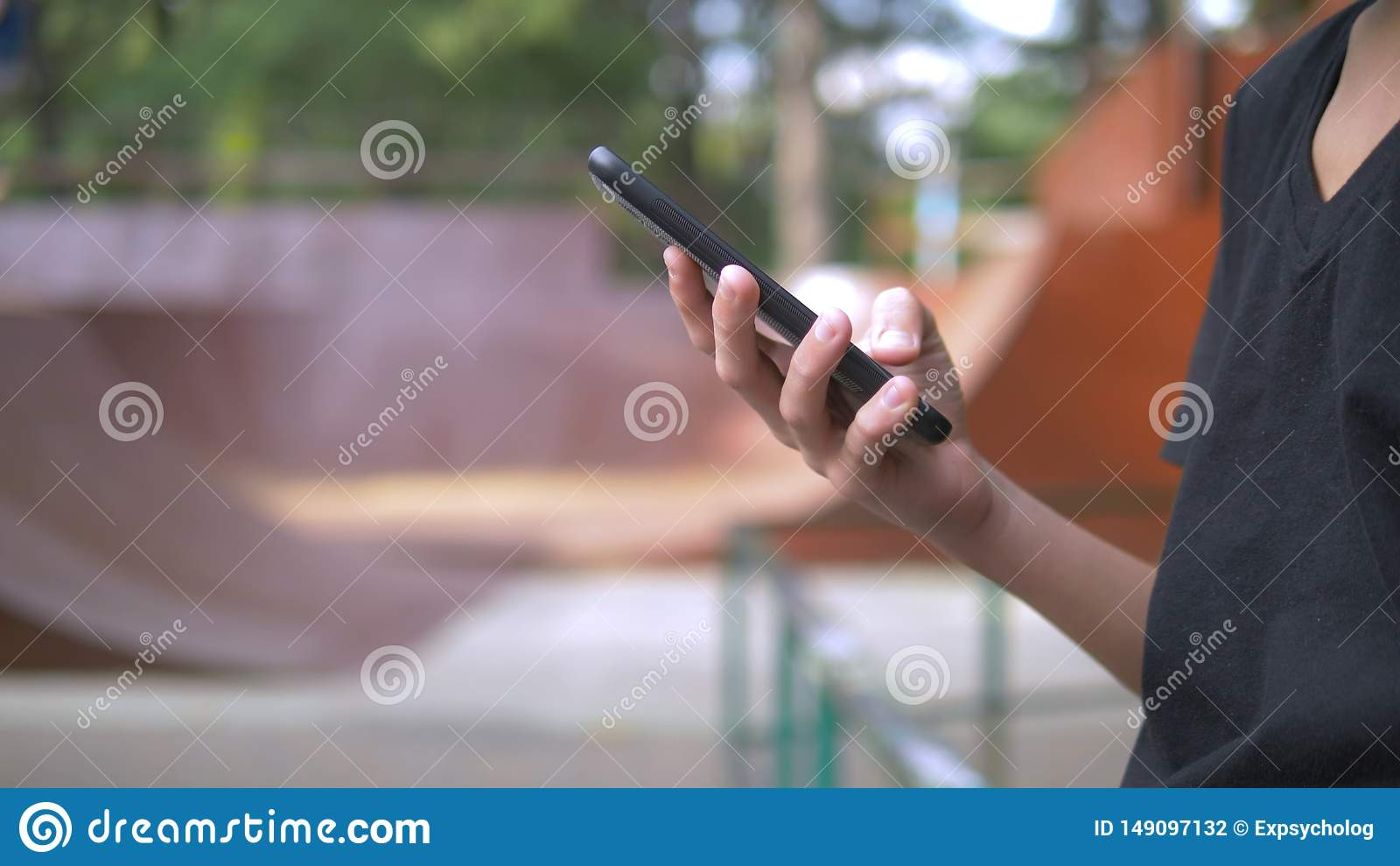 Αγόρι εφήβων μόνο που χρησιμοποιεί ένα κινητό τηλέφωνο στα πλαίσια ενός πάρκου σαλαχιών ενώ άλλα παιδιά χαλαρώνουν ενεργά