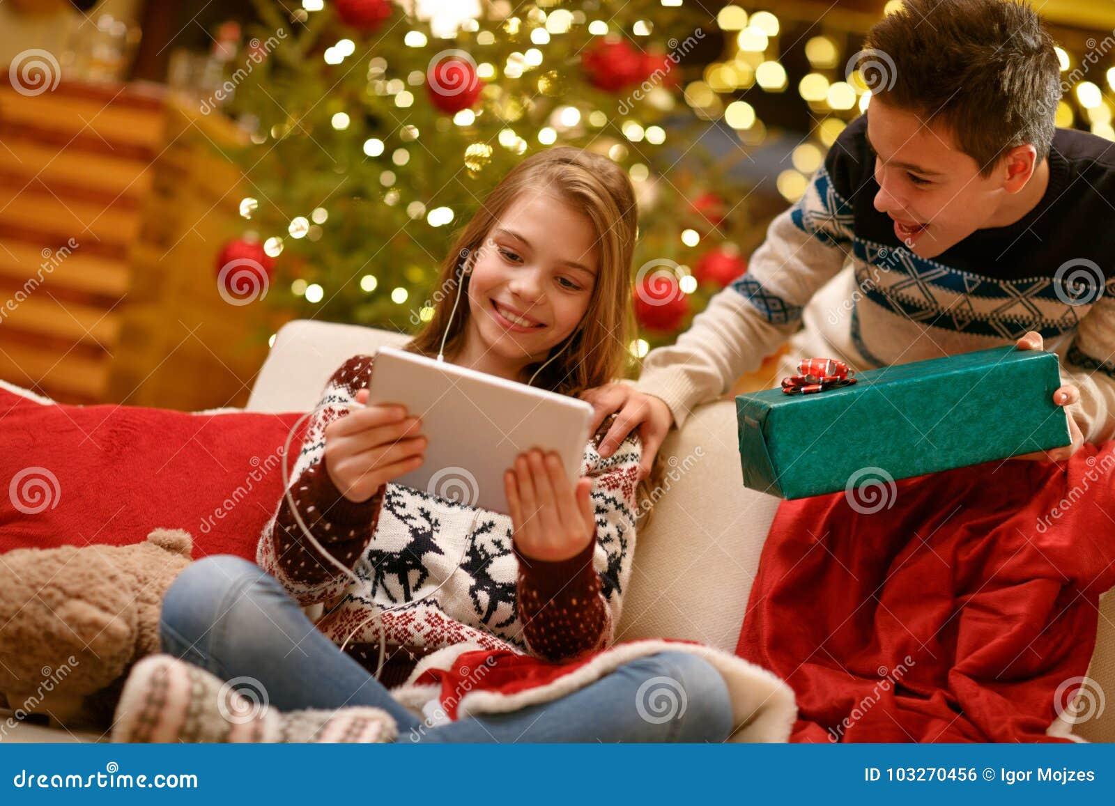 Αγόρι και κορίτσι που απολαμβάνουν στα δώρα Χριστουγέννων μουσικής